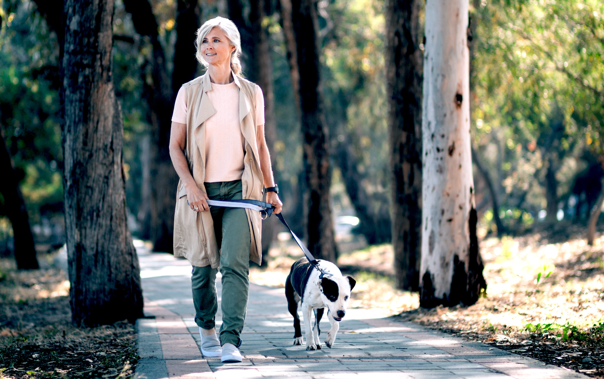 Woman walking black and white dog in the woods
