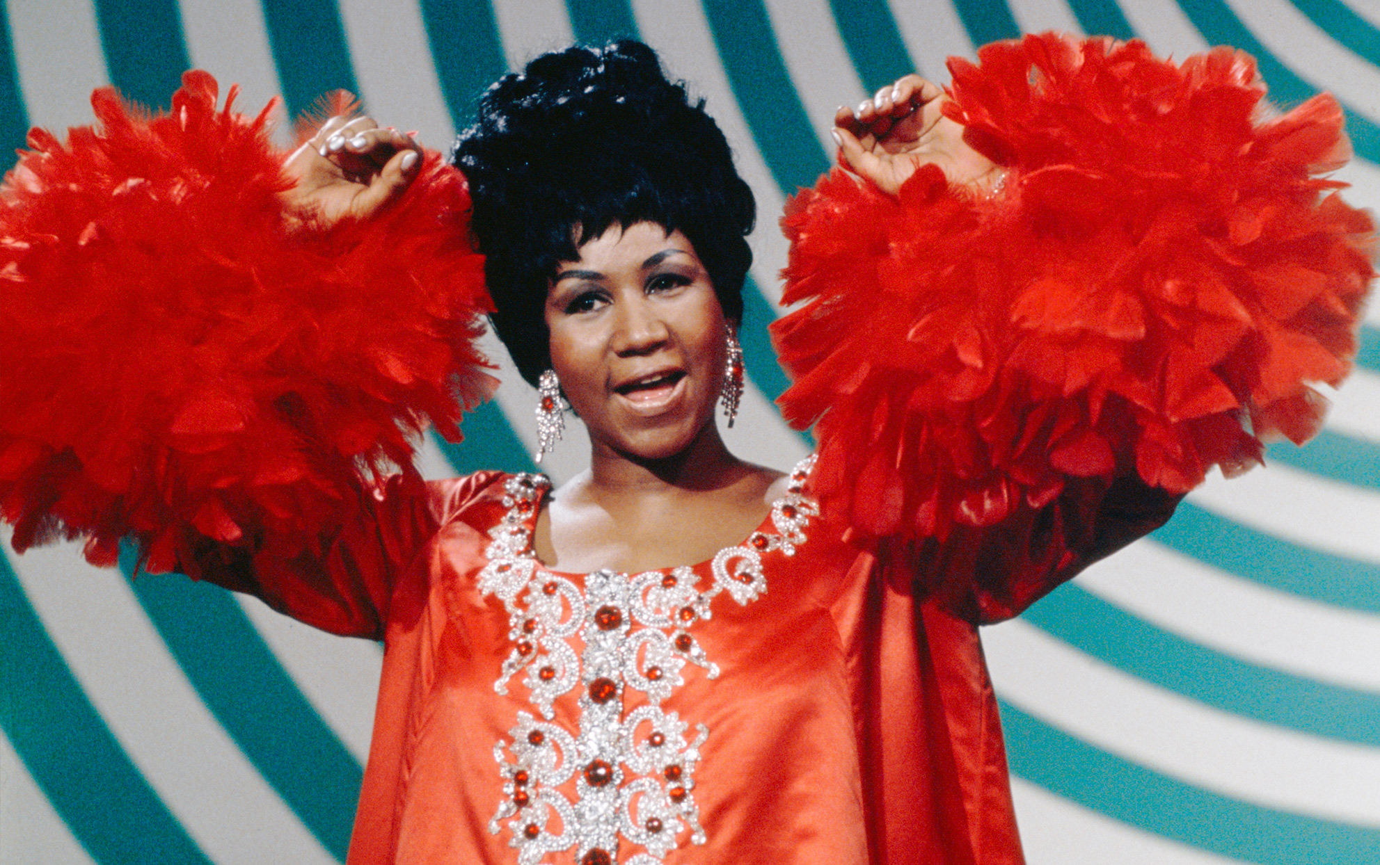 Aretha Franklin in a red dress with a turquoise background