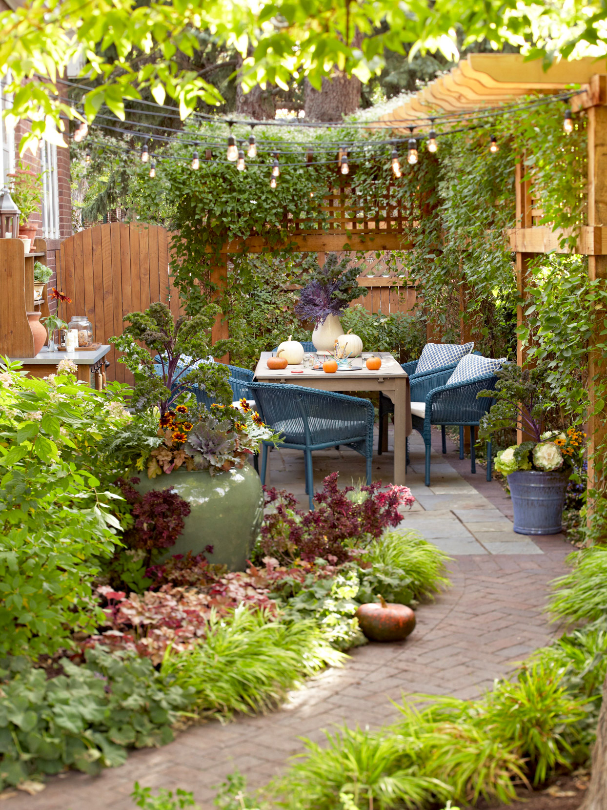 lush garden walk with patio and trellis and string lights