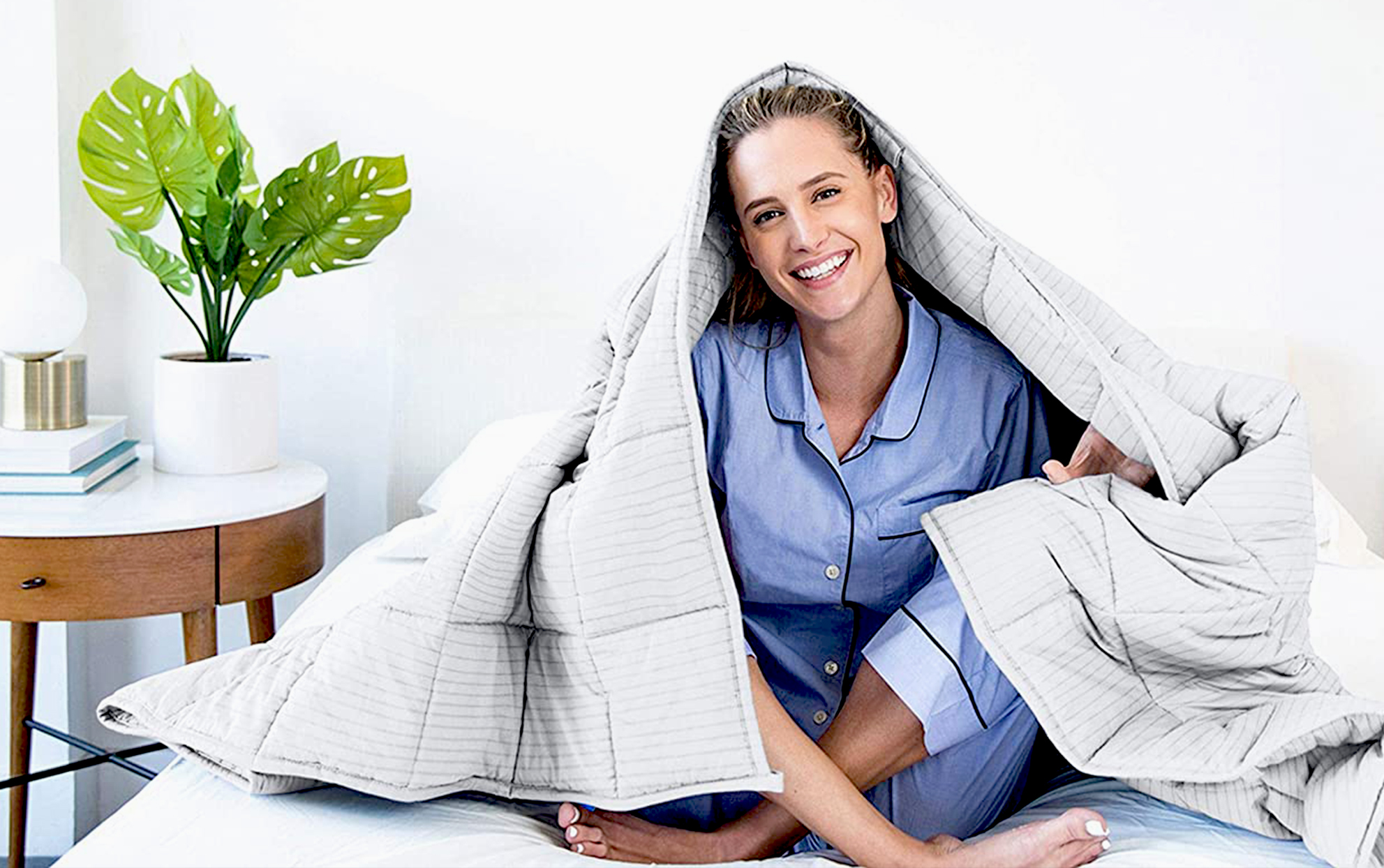 Woman underneath a weighted blanket on a bed