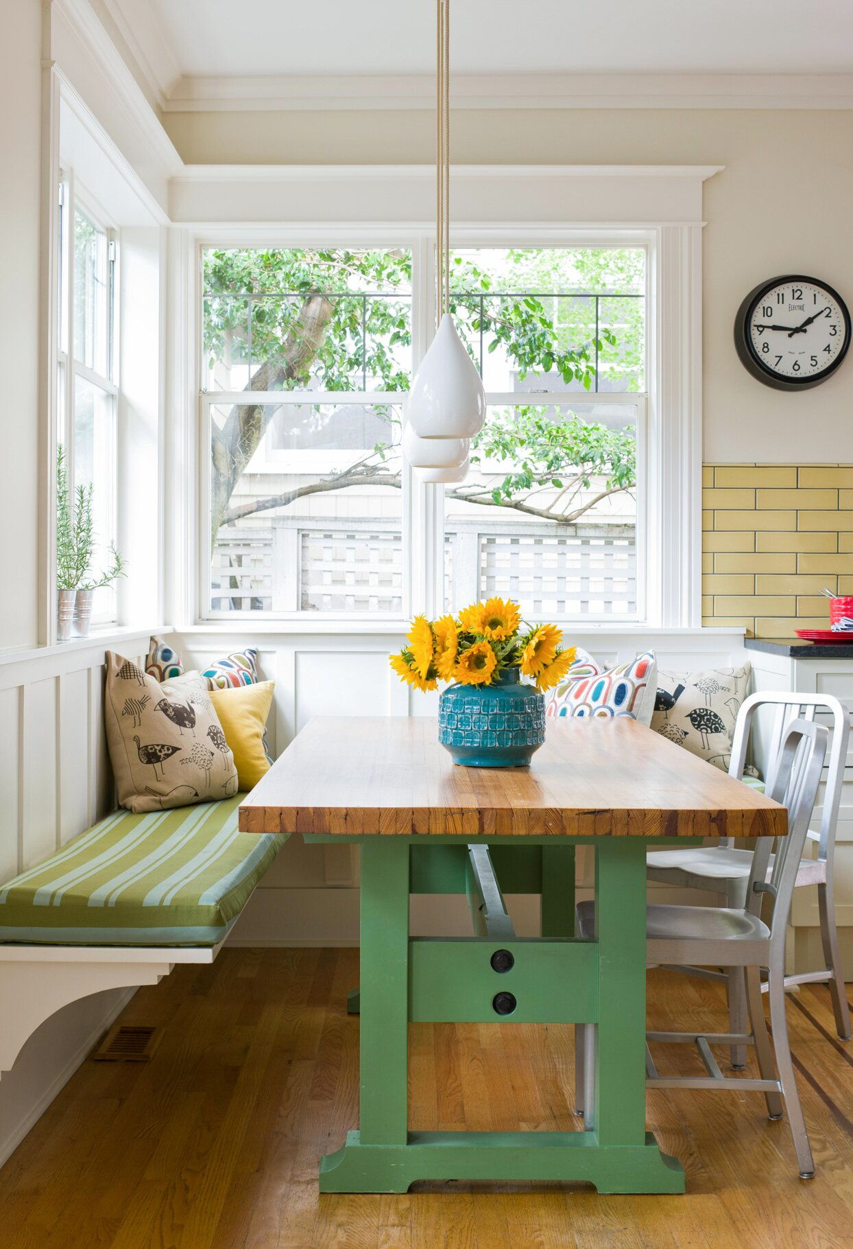 kitchen breakfast nook green table and bench yellow flowers in teal vase
