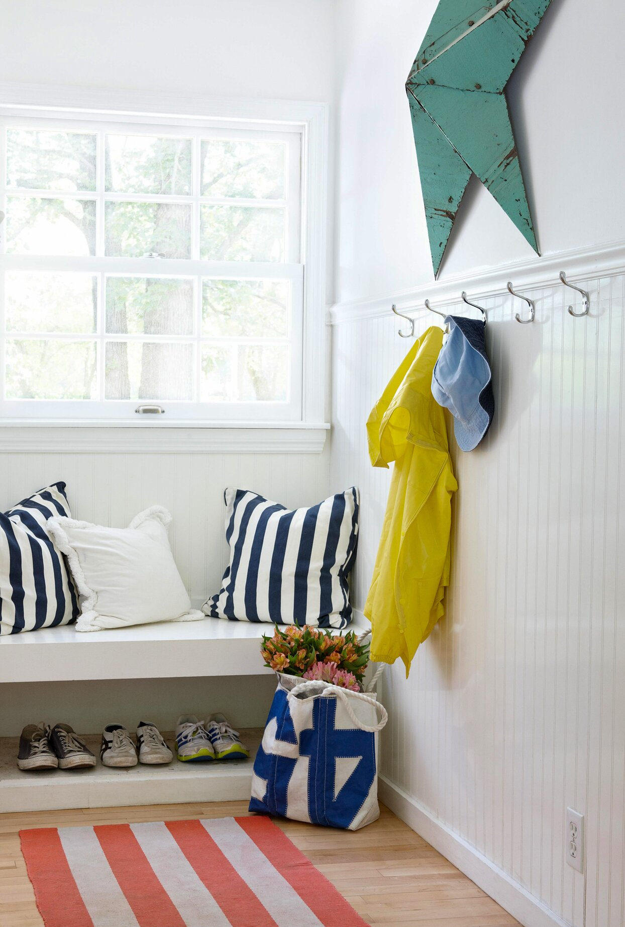 white mudroom bench with pillows shoe storage below