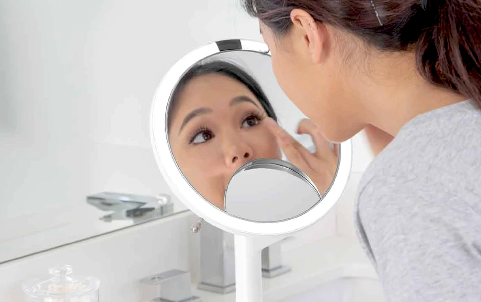 Woman looking into a white vanity mirror