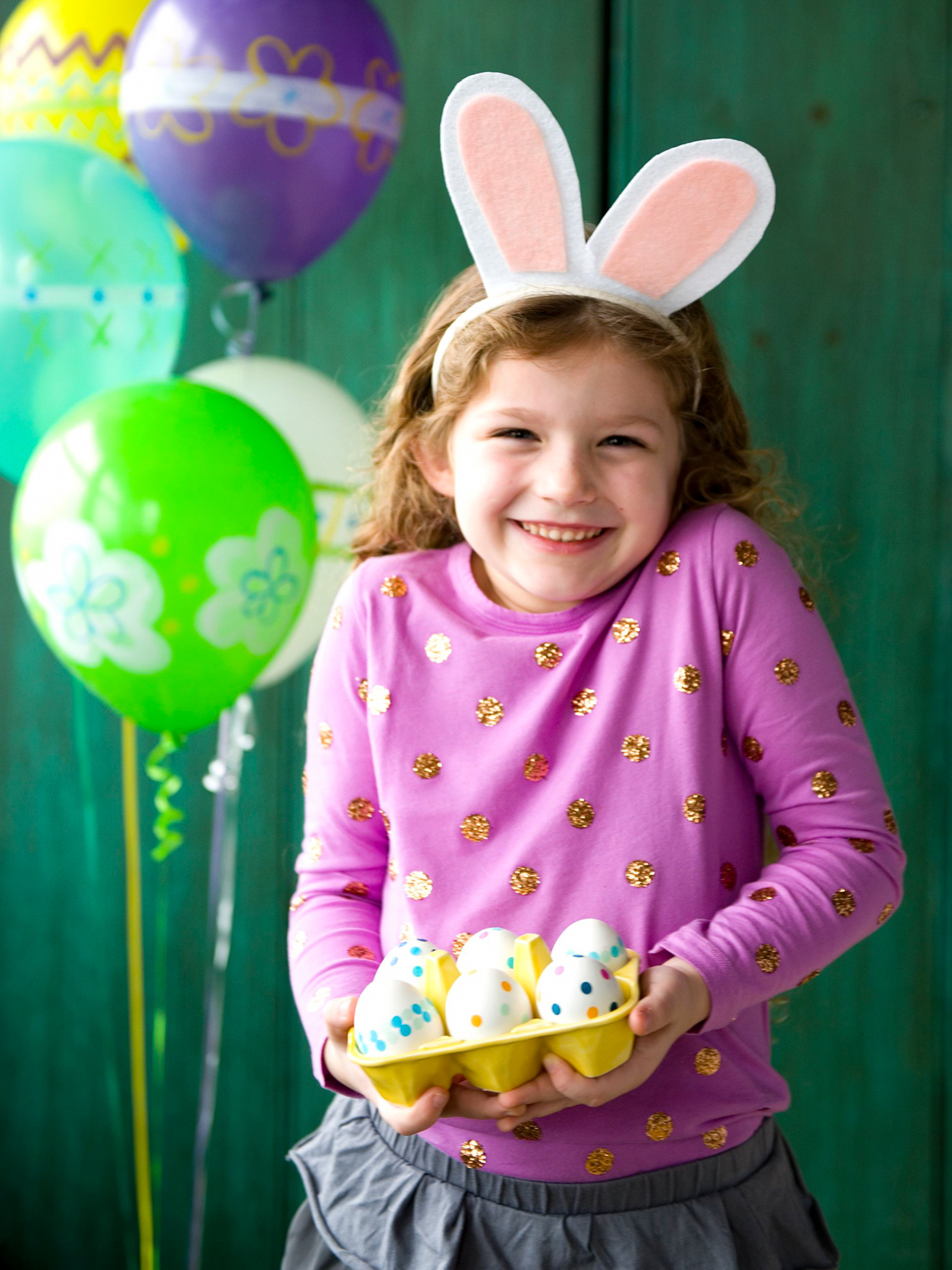 girl wearing bunny ears holding easter eggs