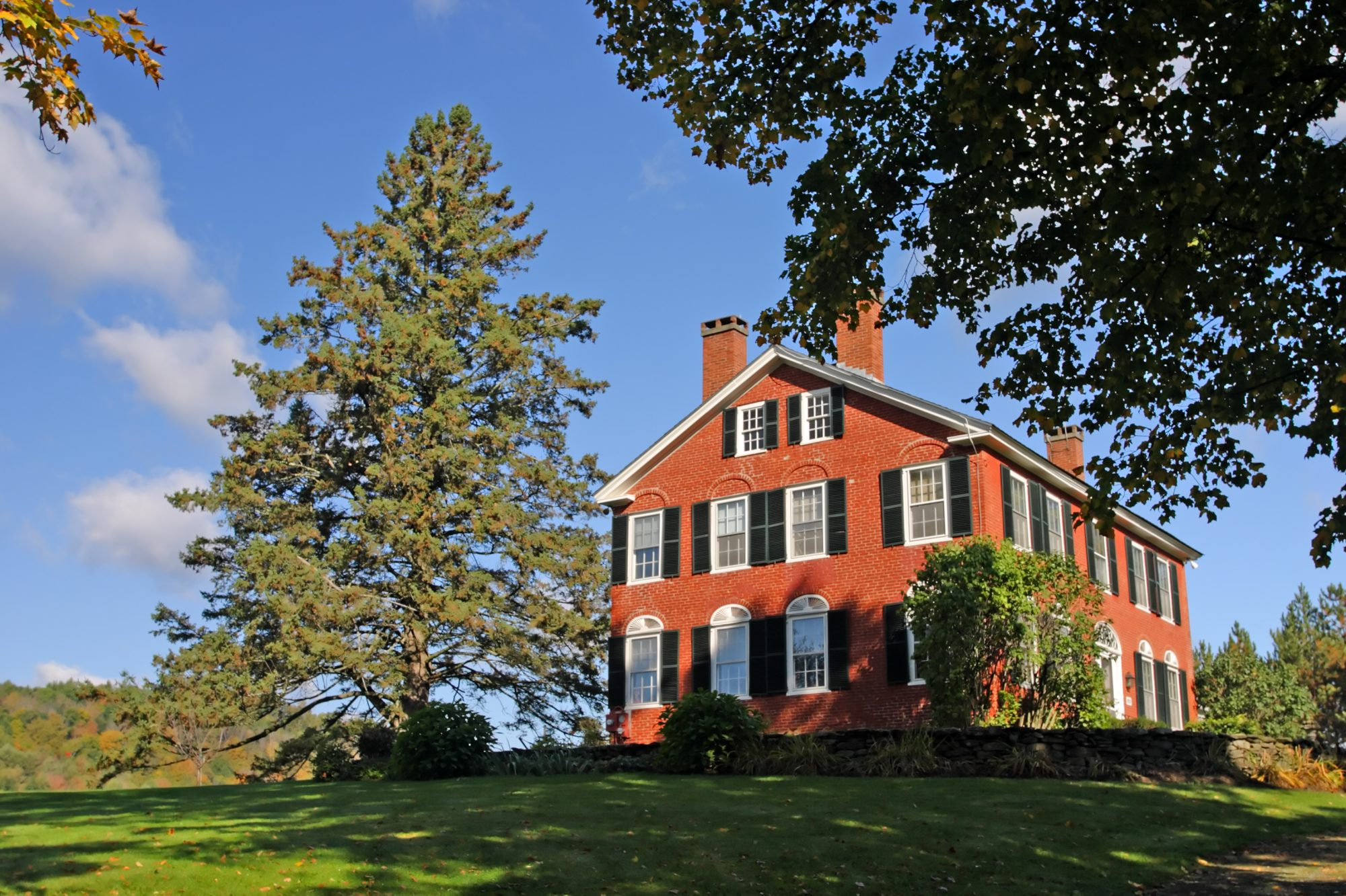 A brick home on a hillside in Vermont with black shutters and large trees surrounding.