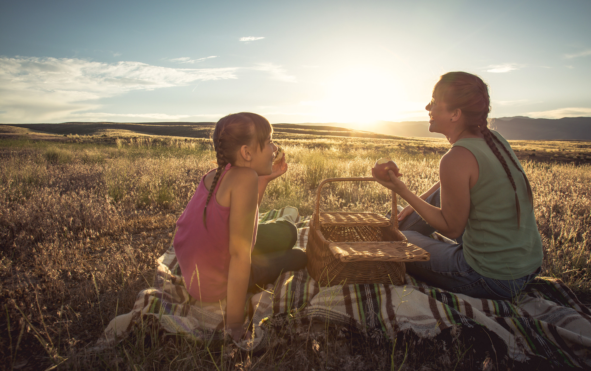 Mother and daughter picnicking in a field