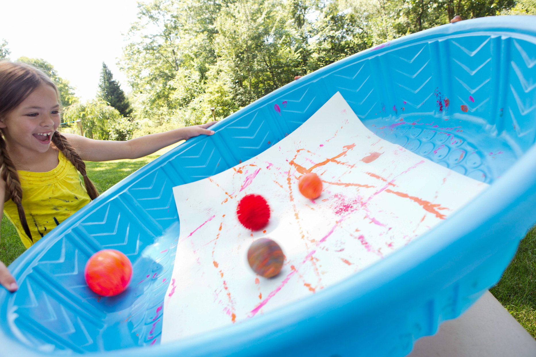 Girl tilting plastic pool with painted balls and paper