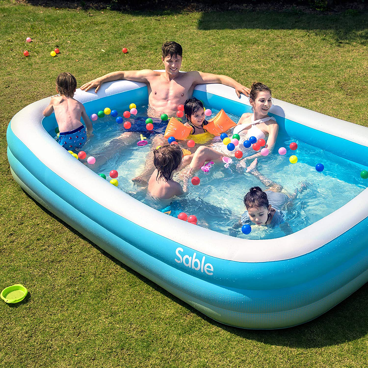family swimming in blue inflatable tool with colorful balls and toys