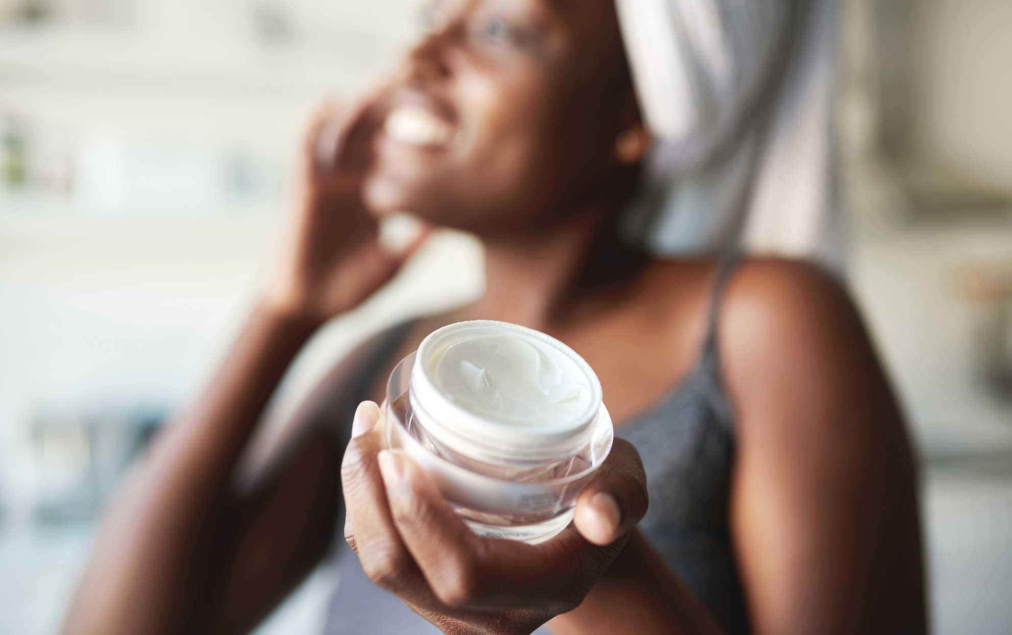 African American woman holding a jar of moisturizer