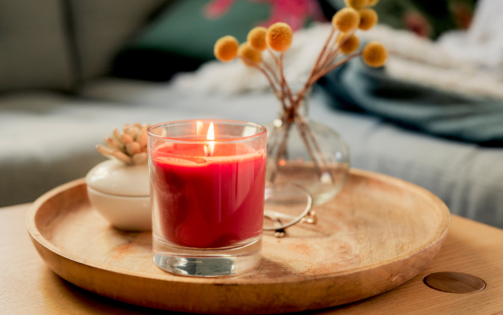 Candle flowers and decorative items on a wooden tray