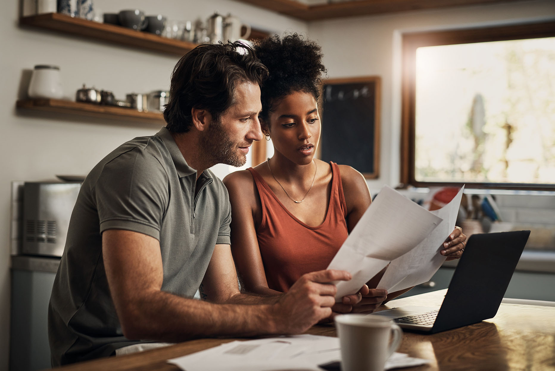 serious looking couple reviewing home refinance applications in their kitchen
