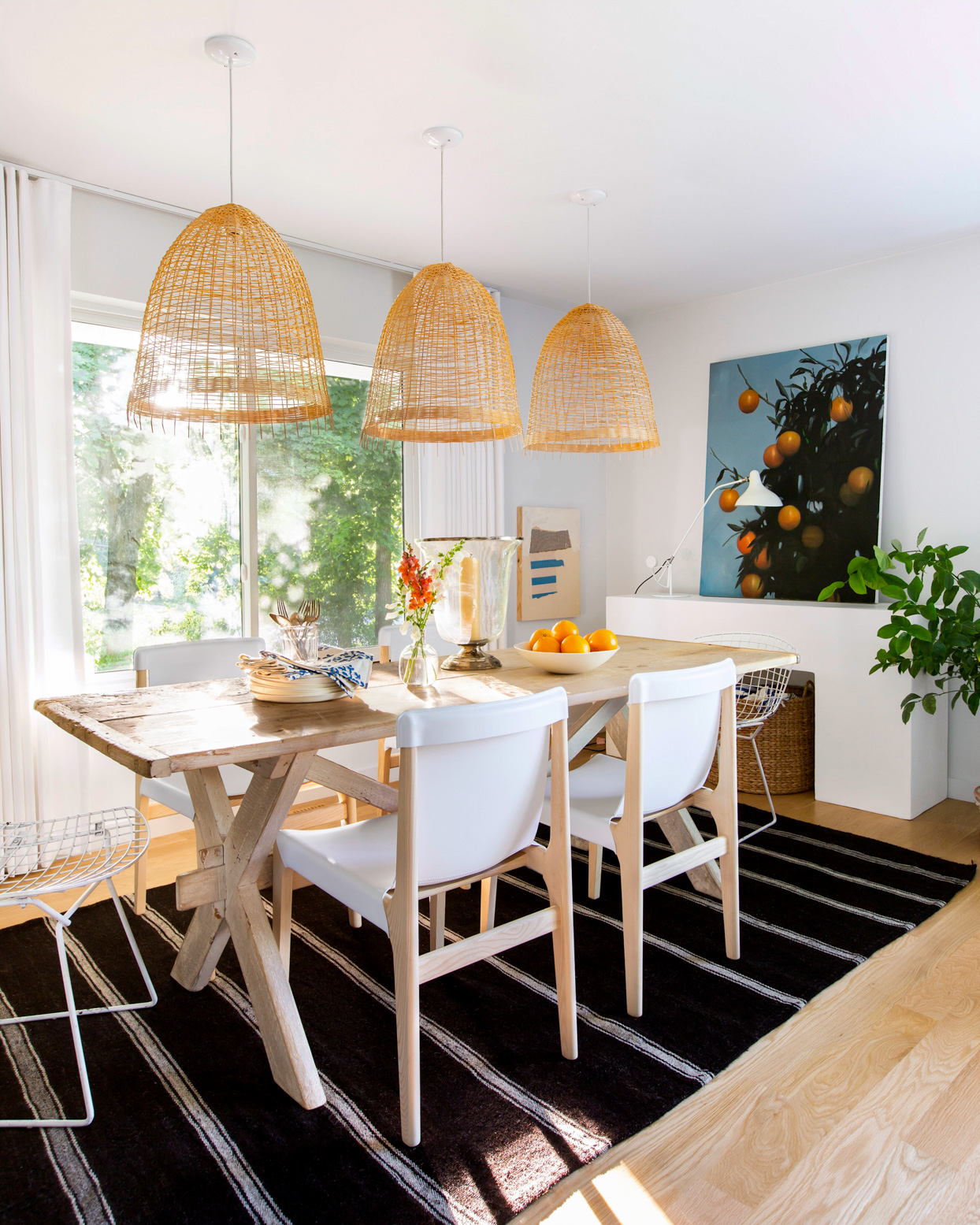 airy white kitchen with light wood and black rug