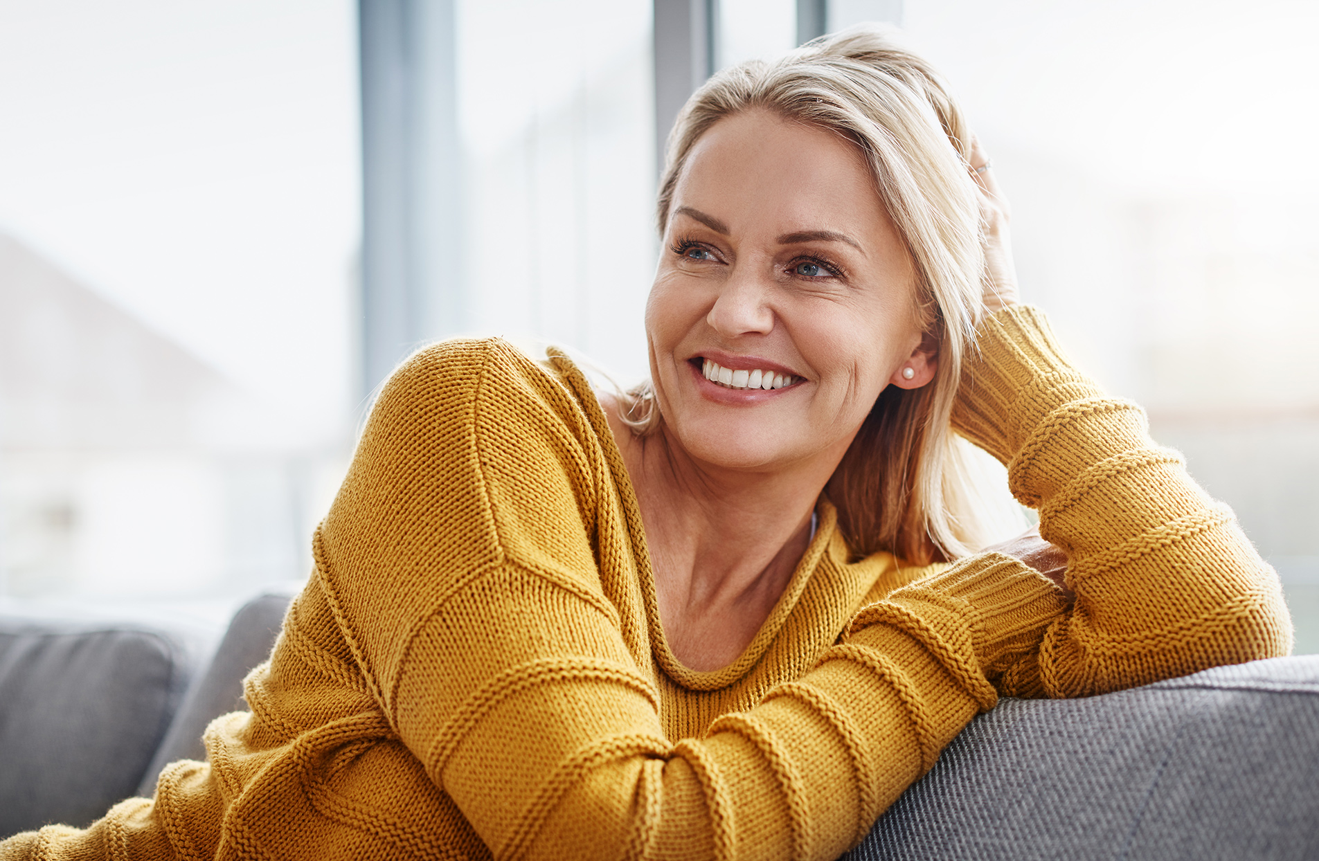 smiling woman wearing yellow sweater and seated on sofa