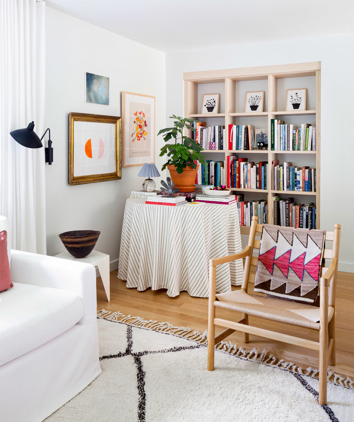 white sitting room with library and colorful art in corner