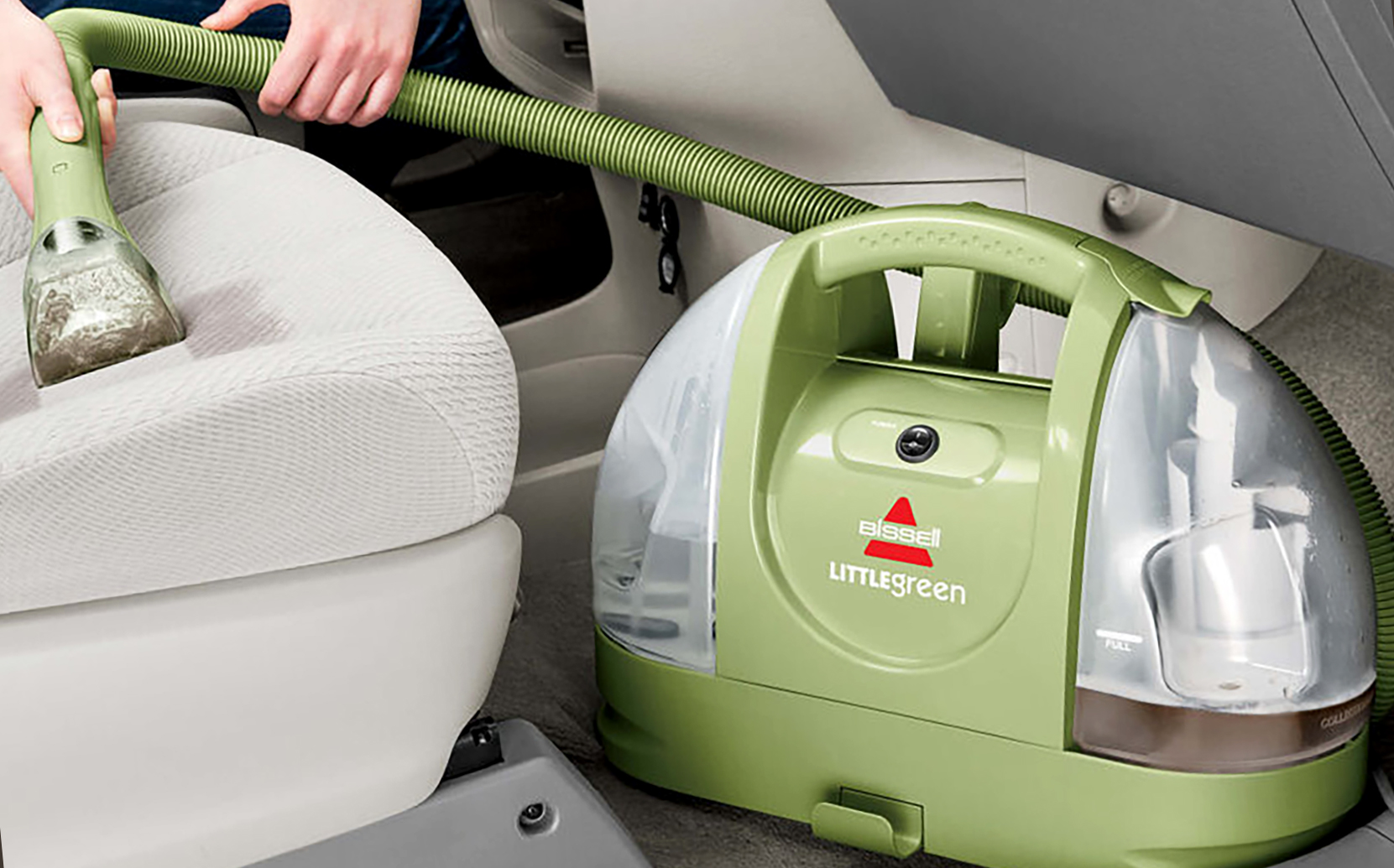 person using portable bissell carpet cleaner inside car