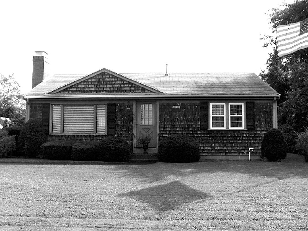 black and white one story house with American flag