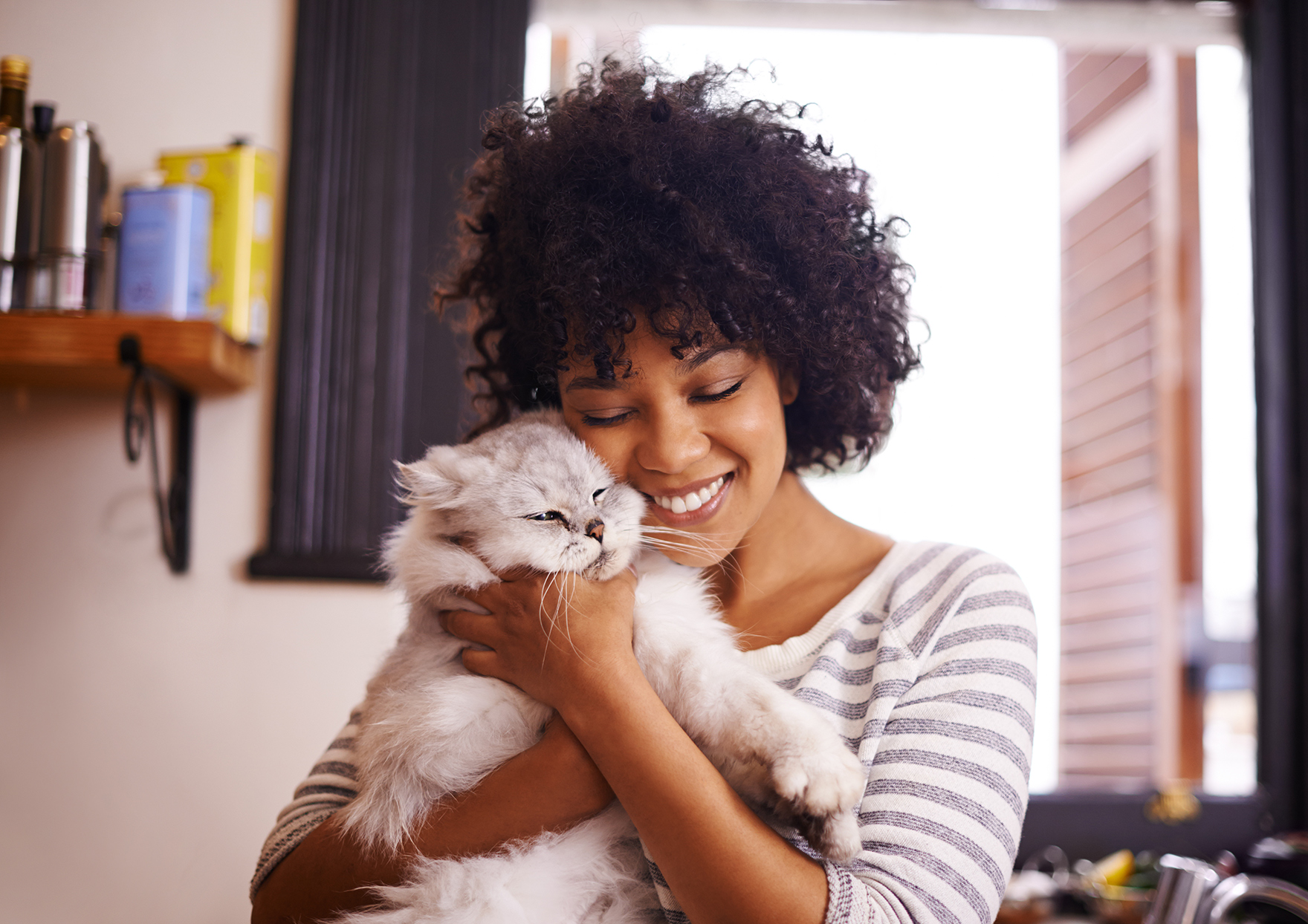 woman holding fluffy cat in her home