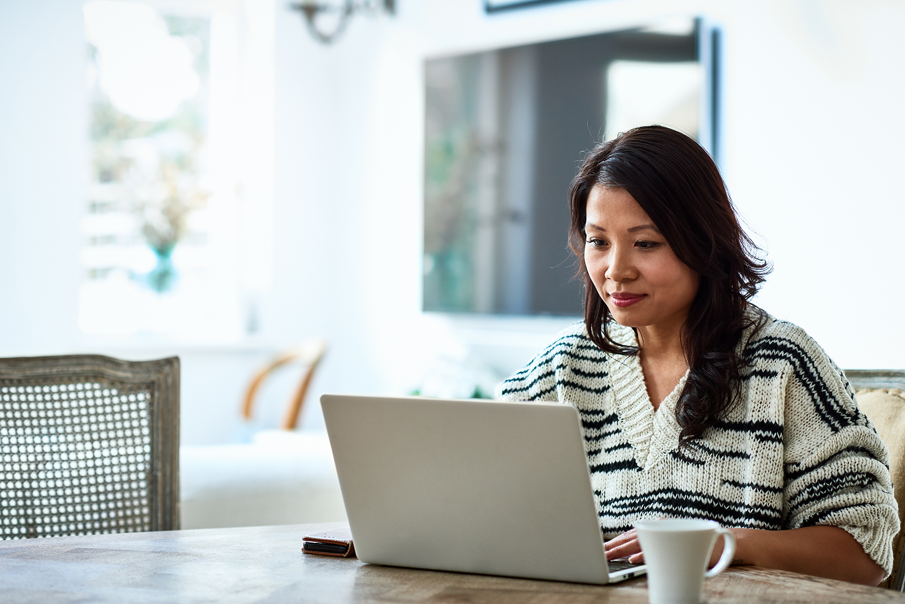 woman seated at table working on computer