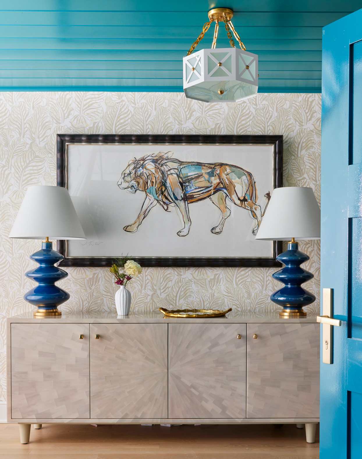 entryway with blue door teal lamps abstract lion artwork credenza