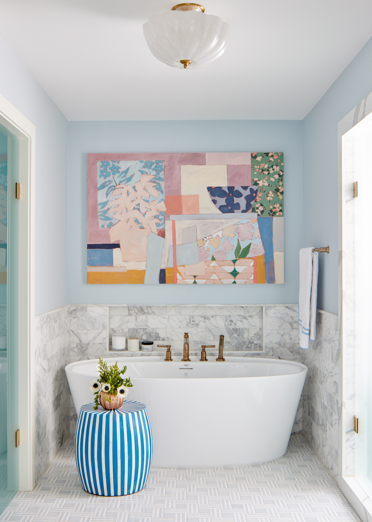 white bathtub with colorful wall art