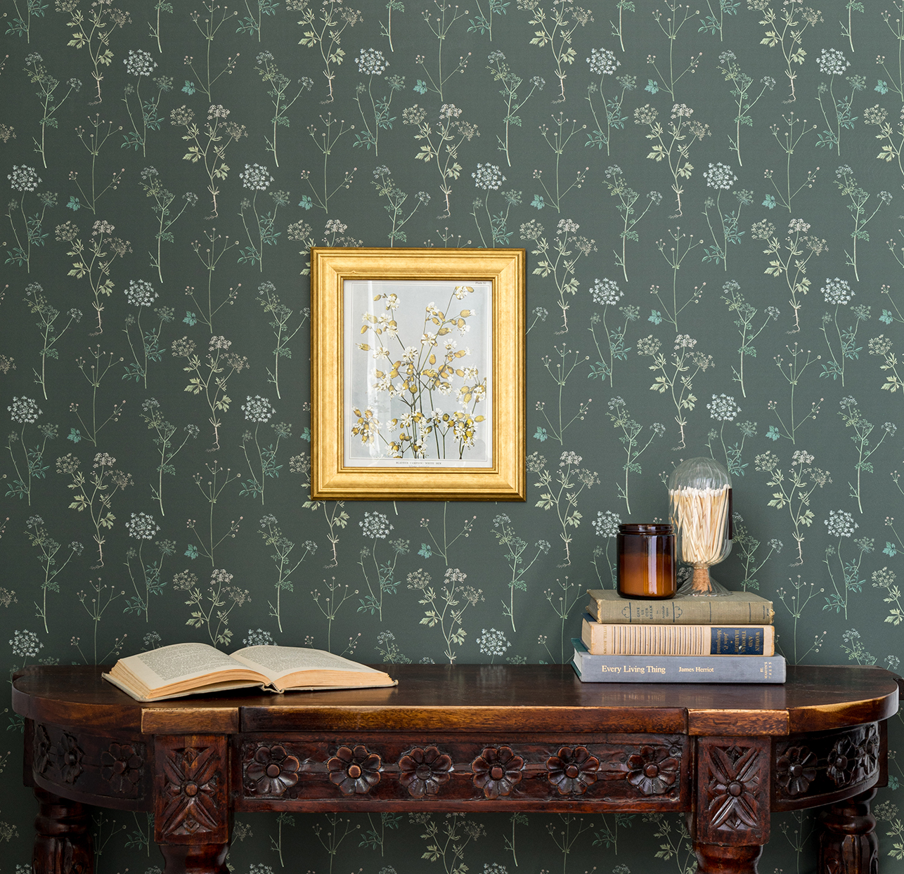 green botanical print wallpaper with framed art and antique table