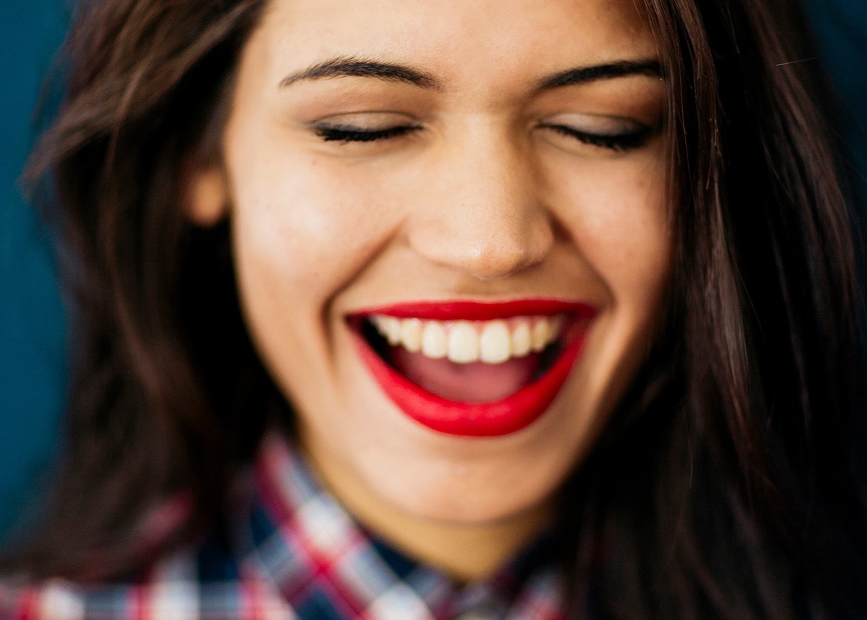 woman with bright red lipstick laughing with her eyes closed