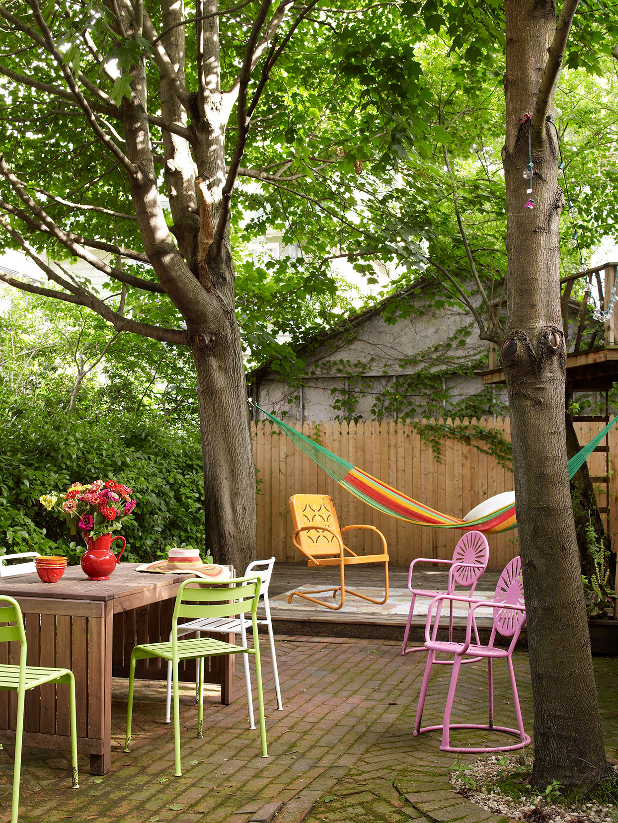 colorful patio chairs and a hammock on brick outdoor patio