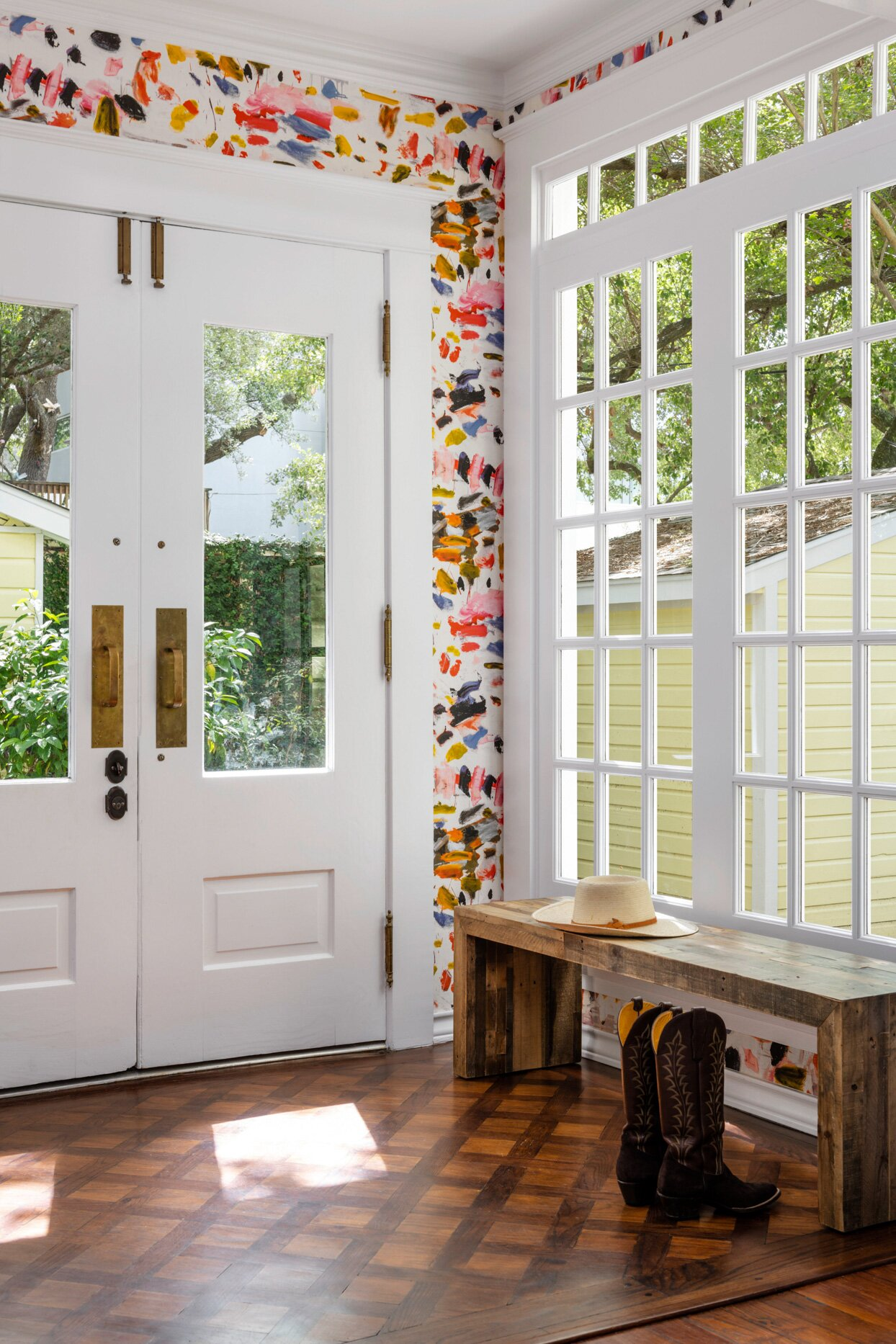 cheery entryway with colorful wallpaper and white doors and windows