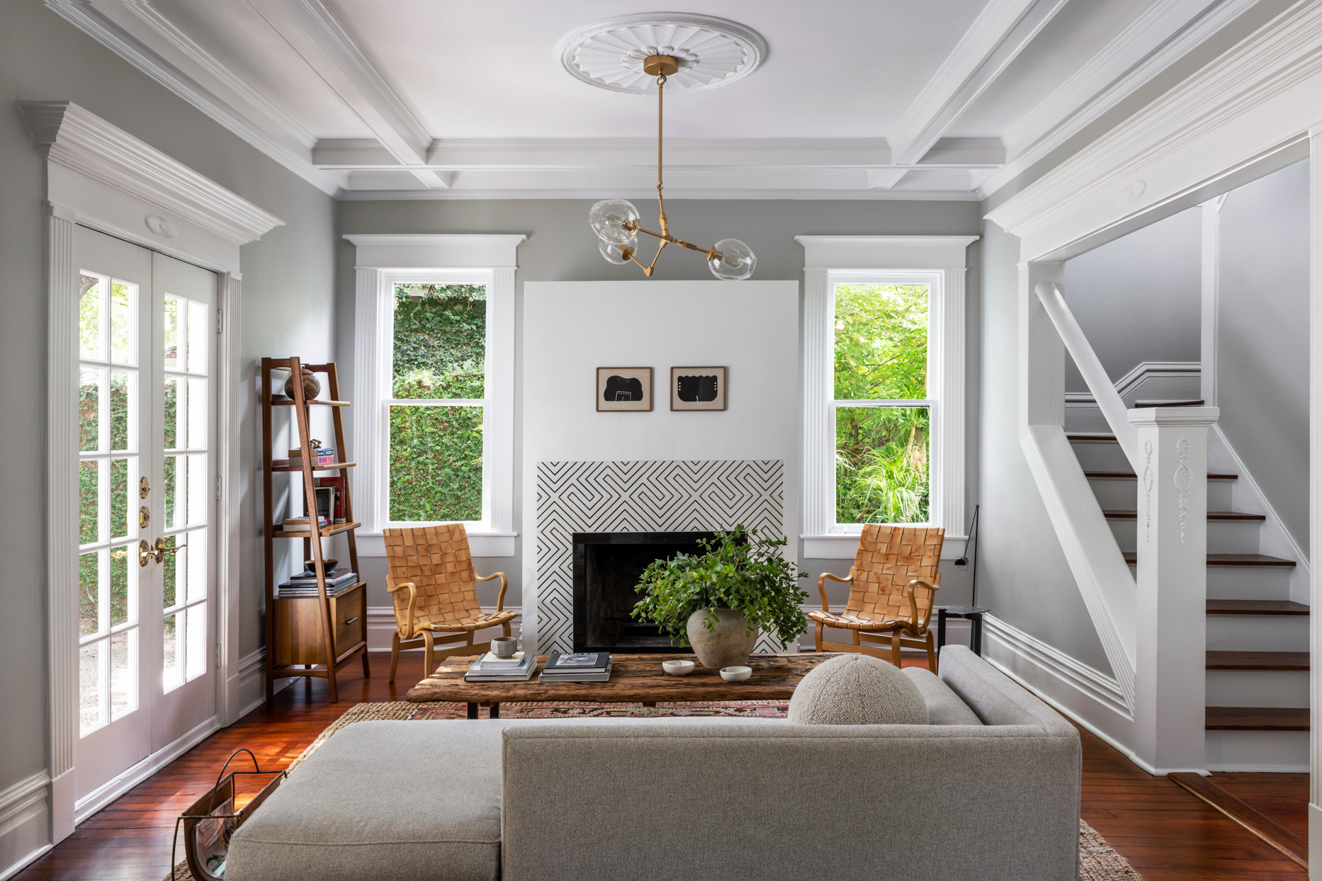gray living room with warm wood floors and modern chandelier