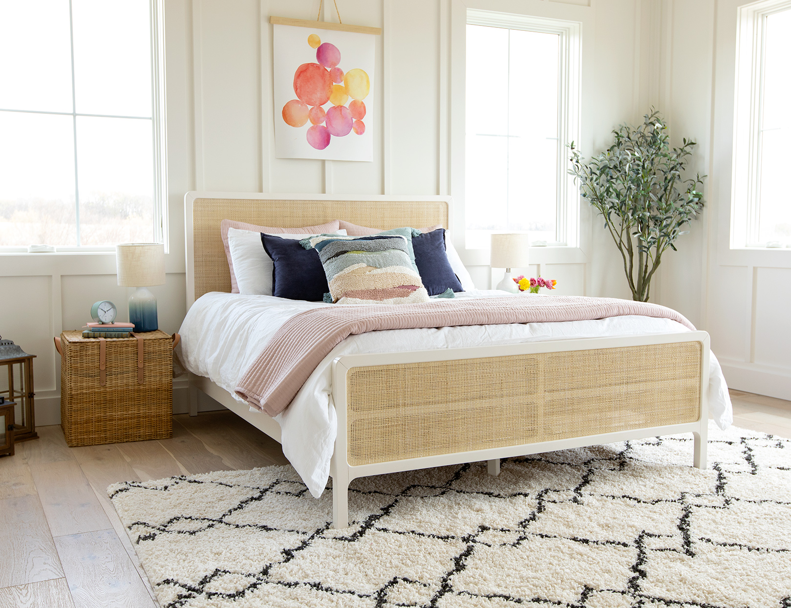 bright bedroom rattan bed blue pink pillows artwork plant rug