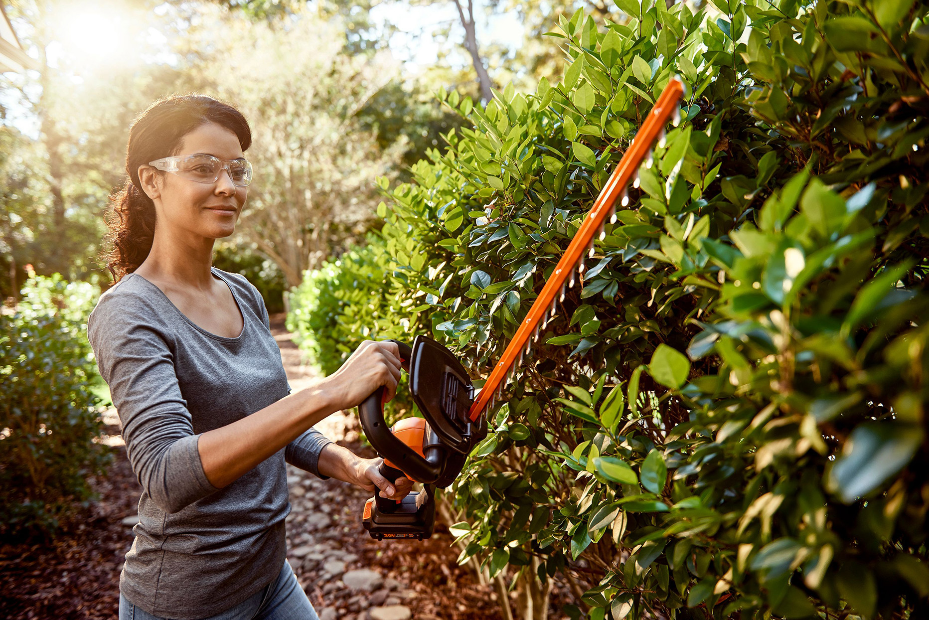 woman using hedge trimmer in yard