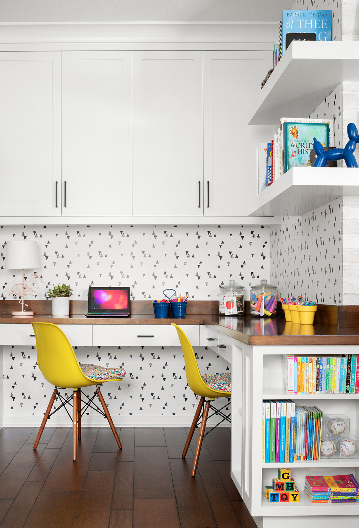 yellow Eames-style chairs corner desk playroom shelving graphic wallpaper