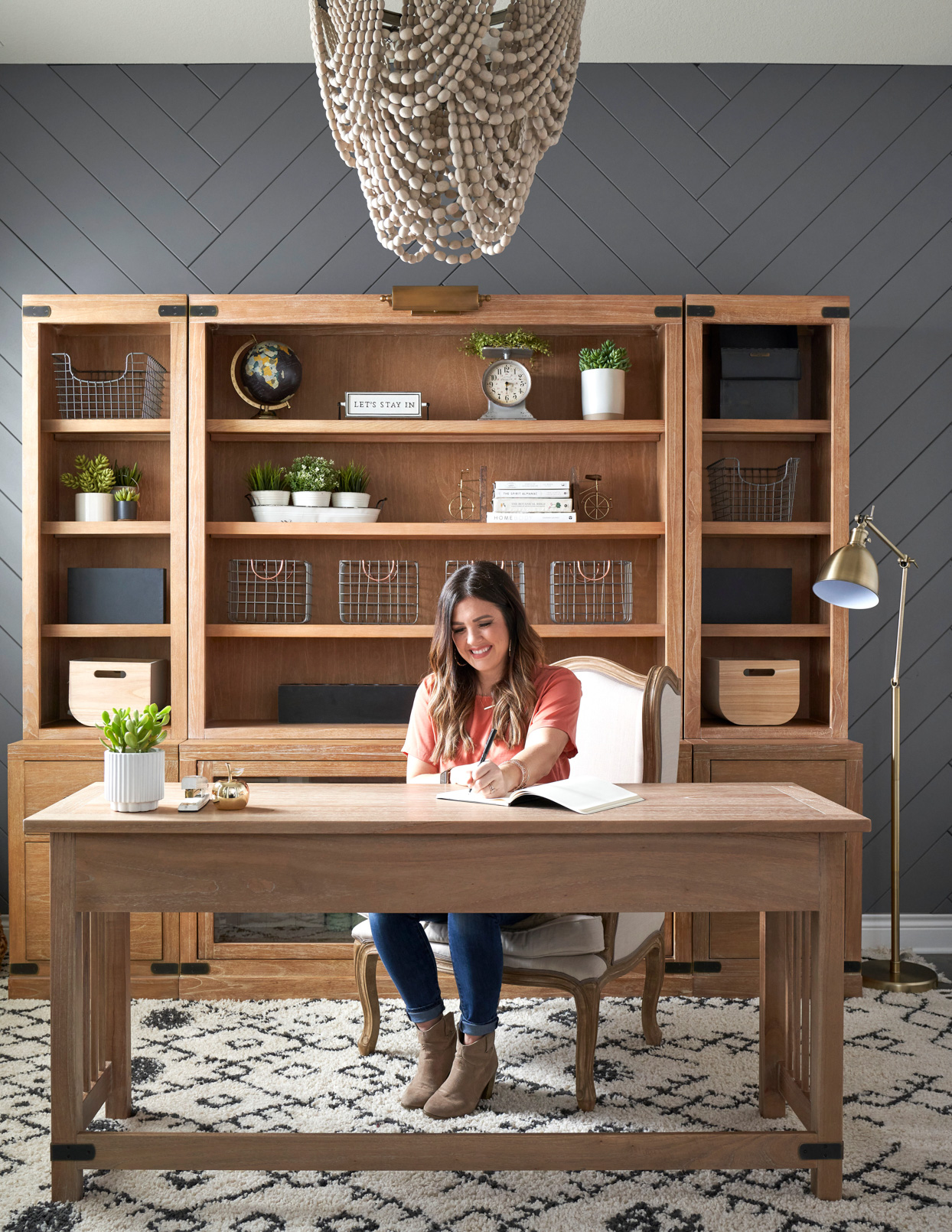 adult writing at wooden desk