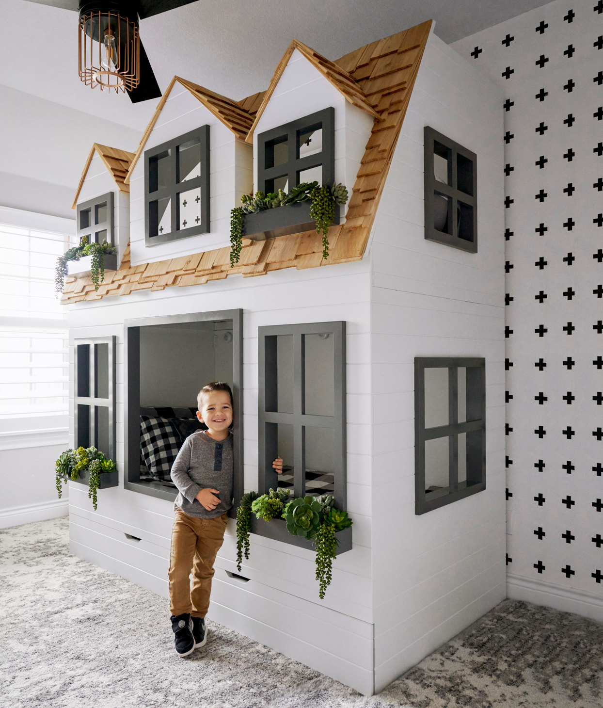 child next to house bunk bed
