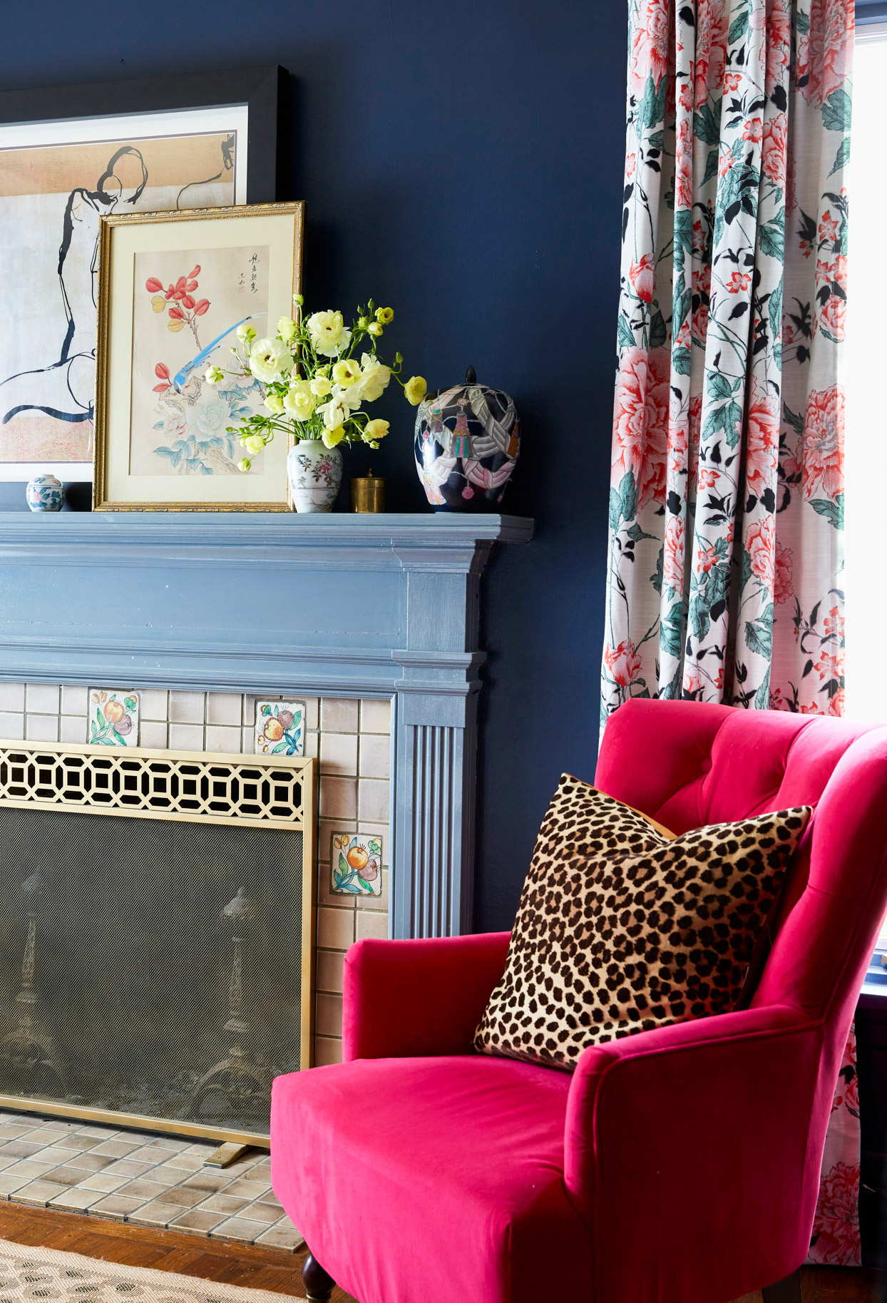 sitting area with dark blue walls and red chair