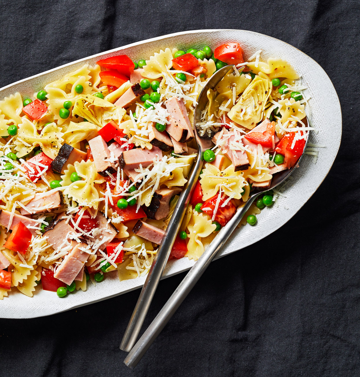 Pasta Toss with Peas and Artichokes on white serving platter