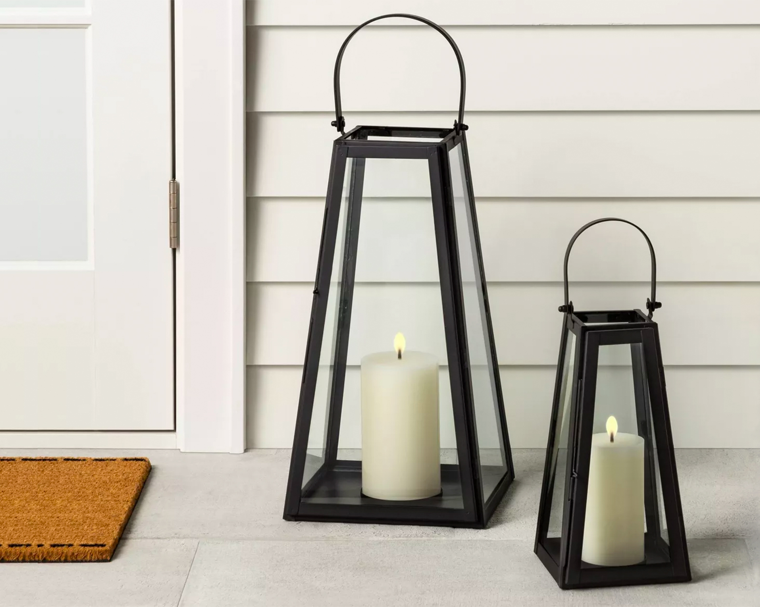 two black metal lanterns with candles by front door