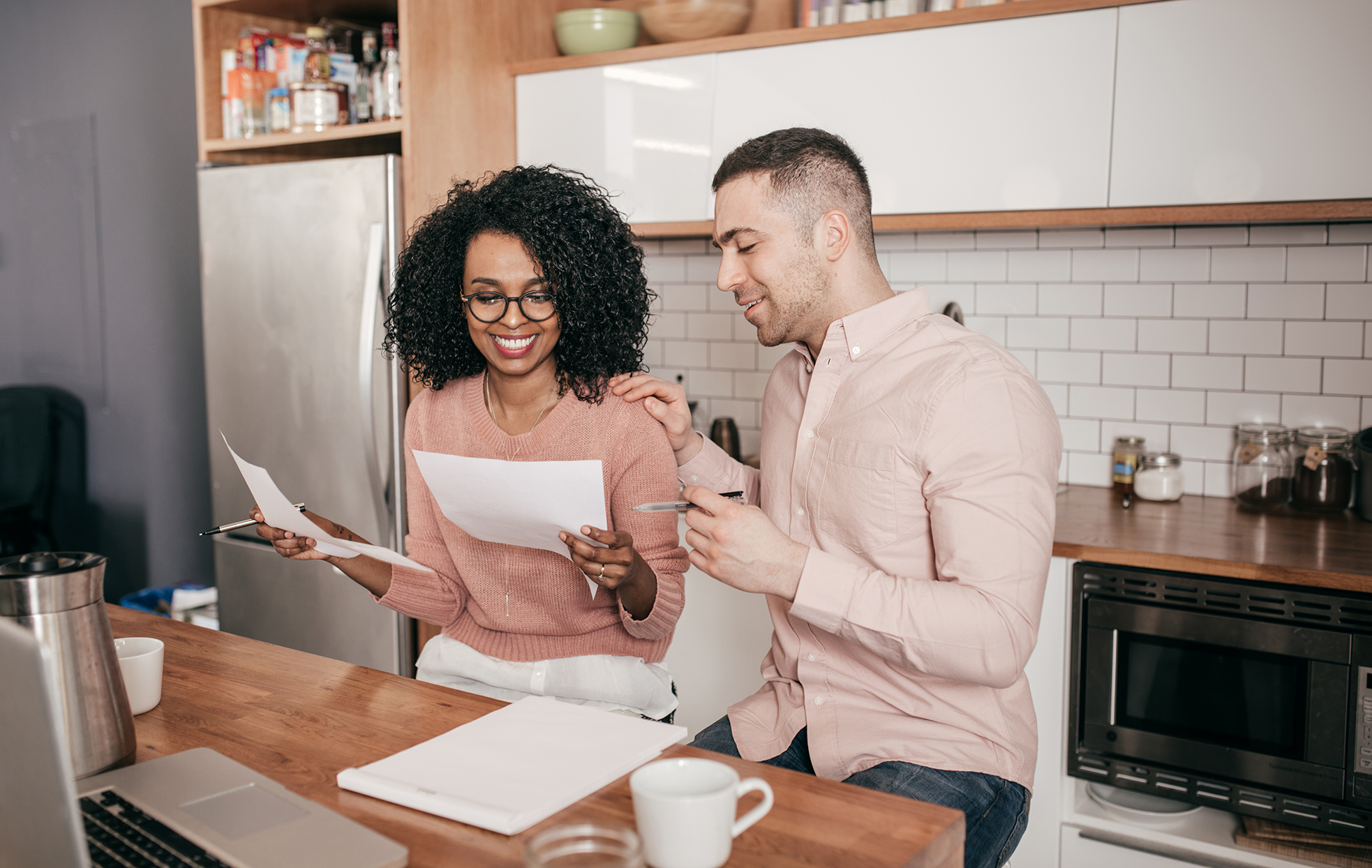 couple reviewing finances in kitchen at home