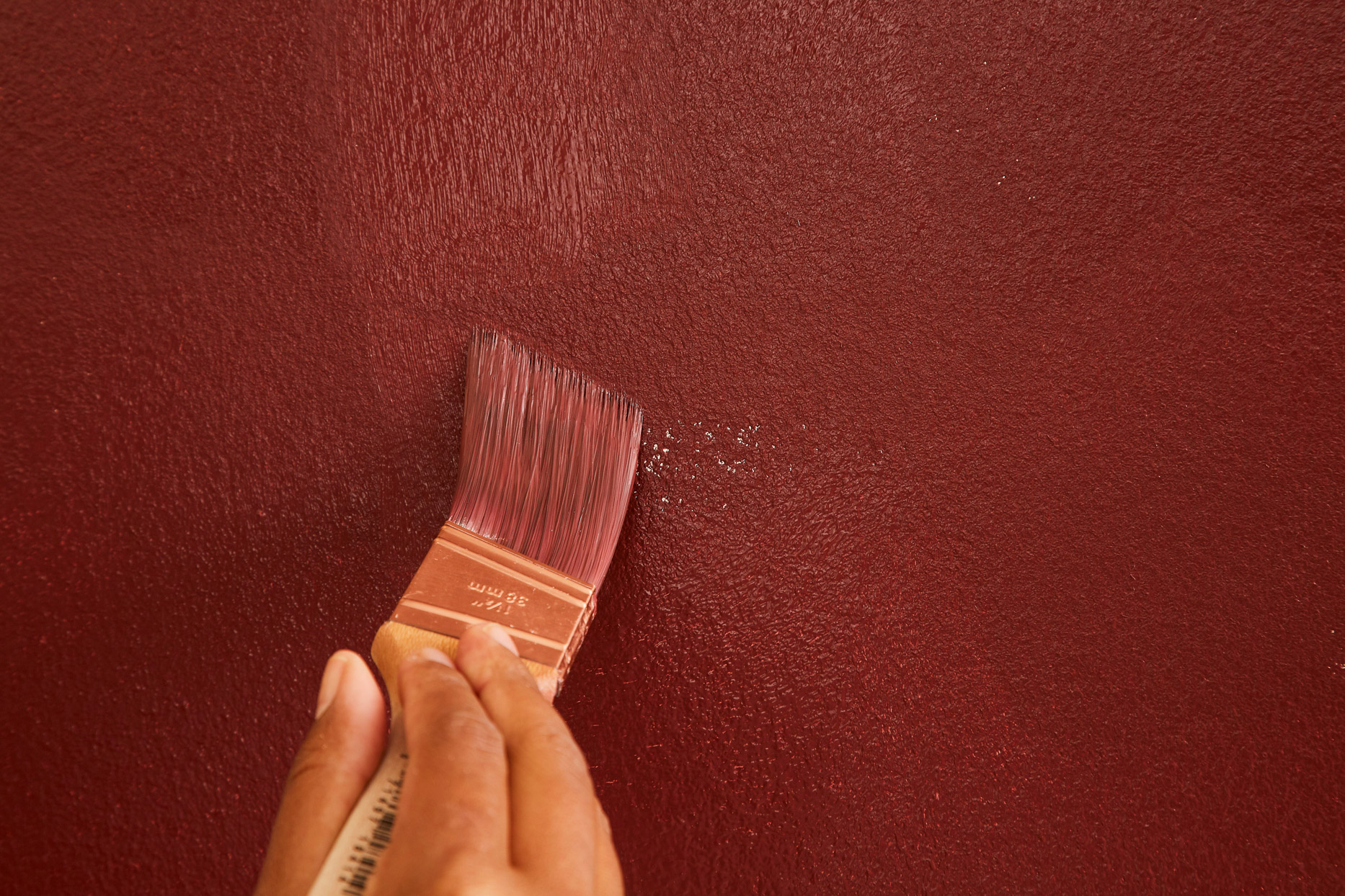 painting wall brown with small brush