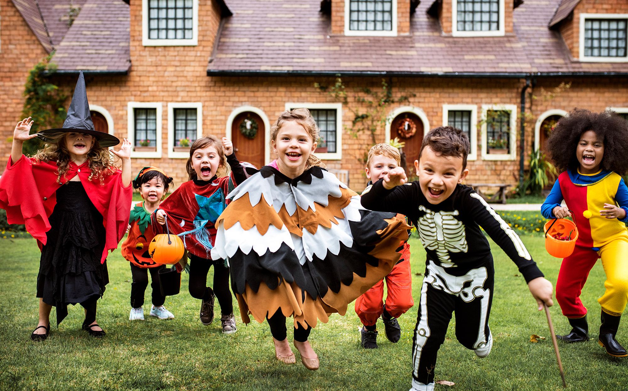 kids wearing halloween costumes in a yard about to go trick or treating