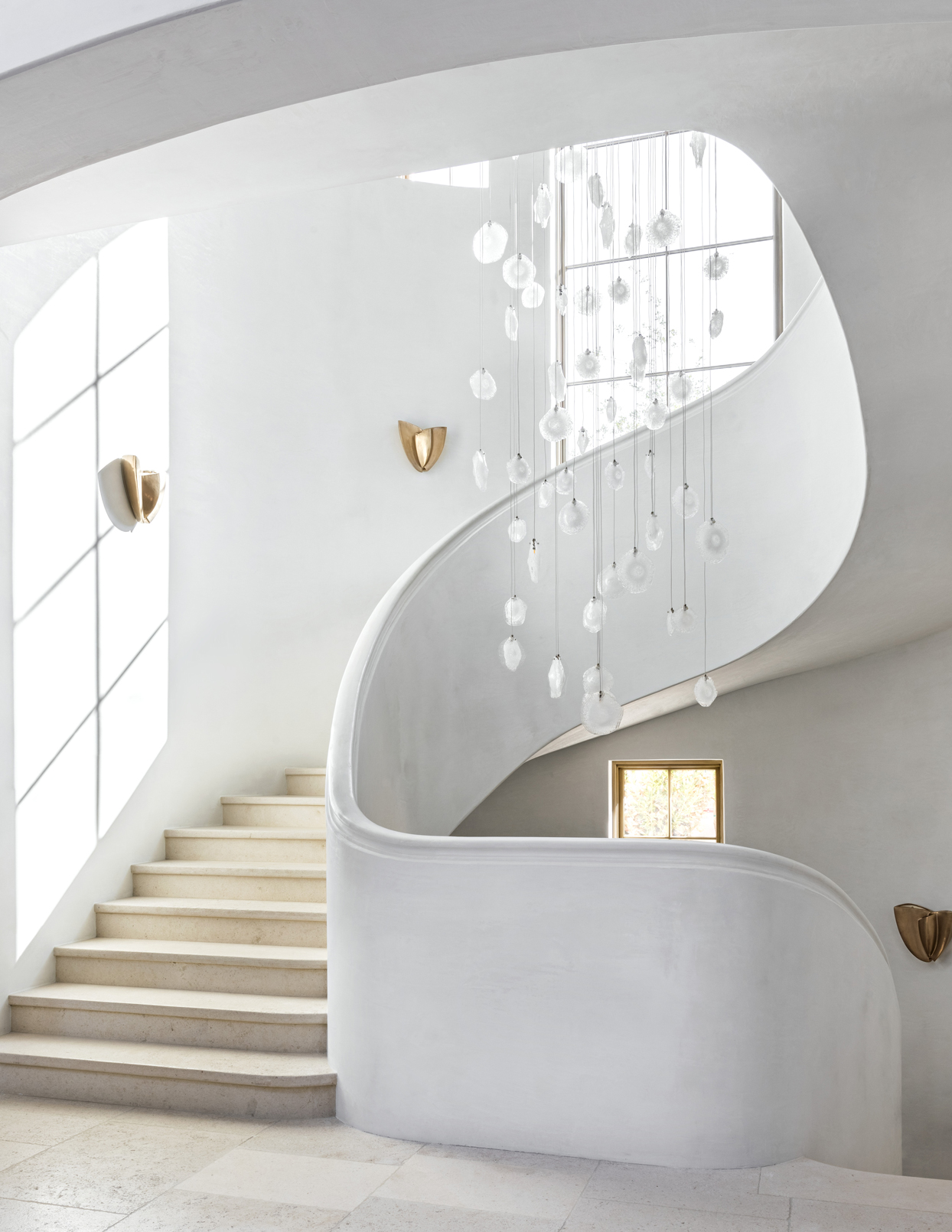curved staircase winds around fixture dangling glass disks