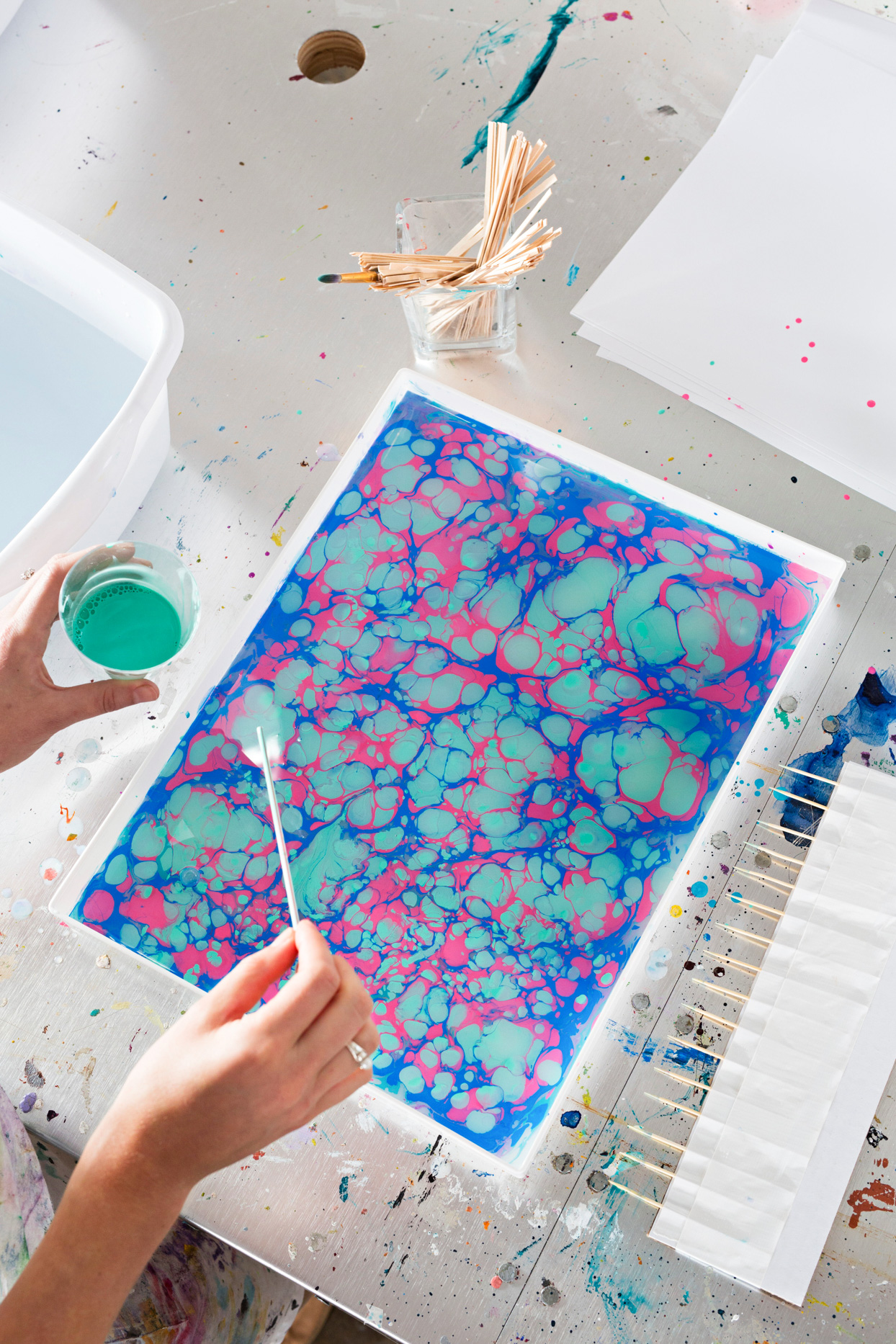 creating blue, green, and pink marble paper