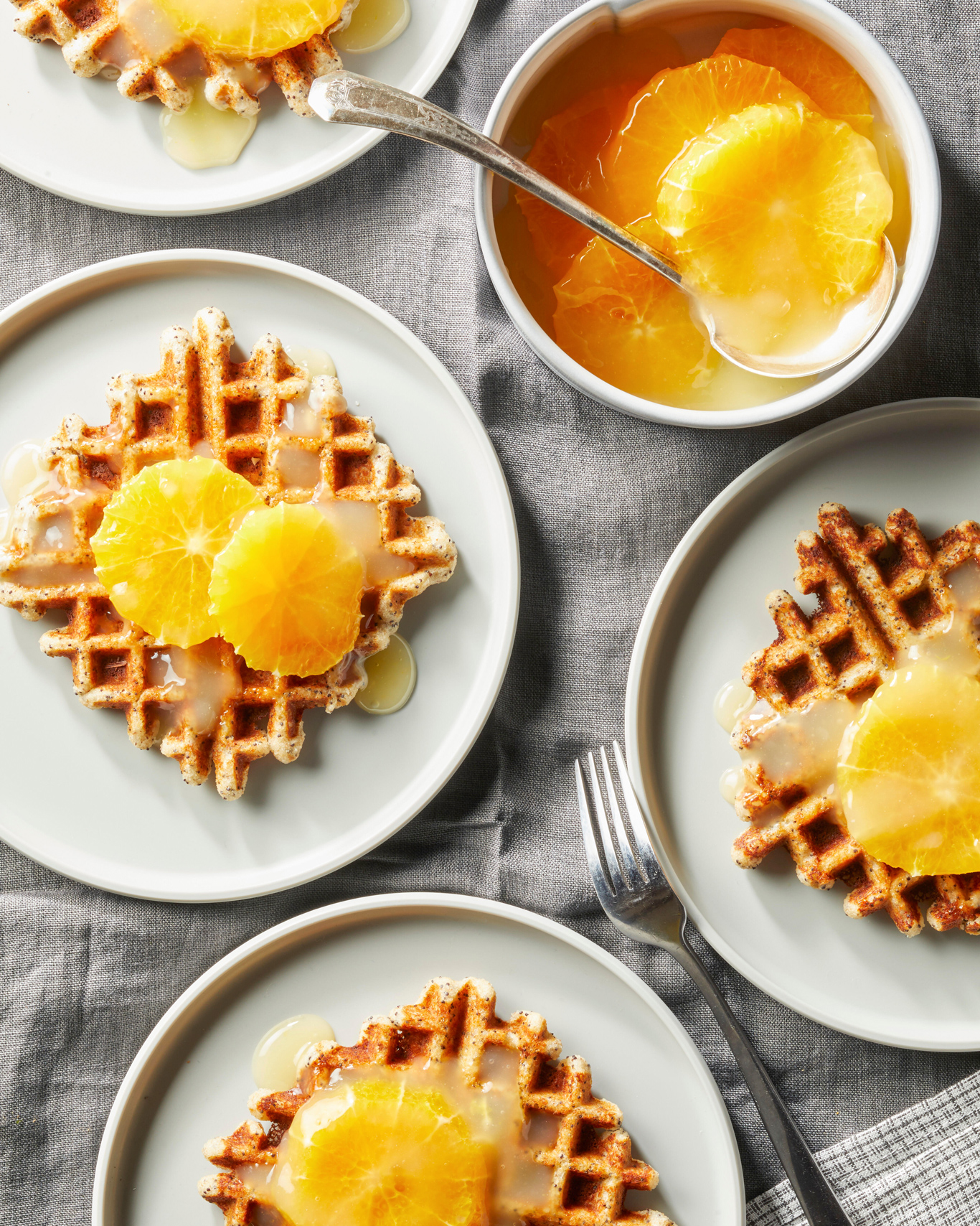overhead view of Poppy Seed Oat Waffles with Citrus Syrup on white plates