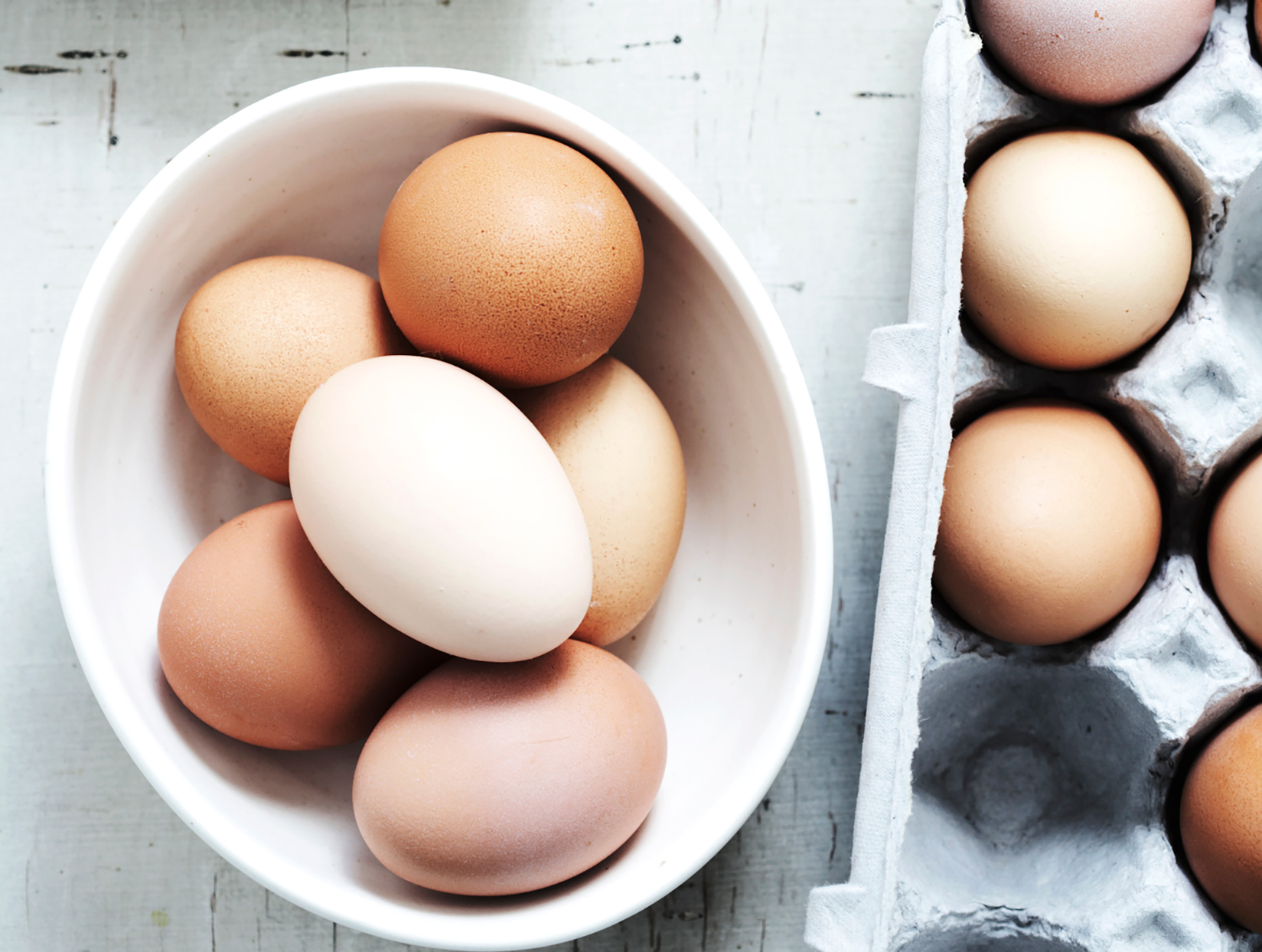 white, and brown eggs in bowl and in carton in a kitchen
