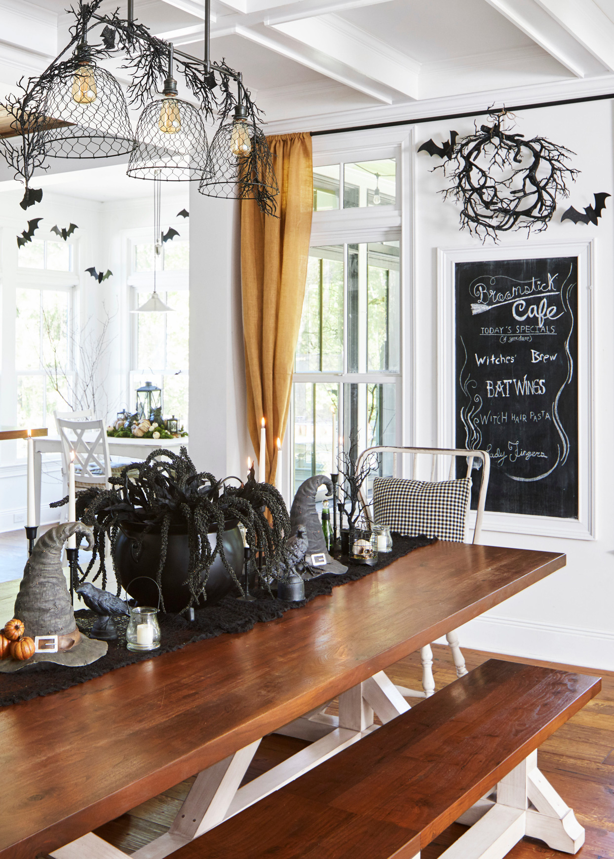 wooden table with festive halloween centerpiece on black table runner