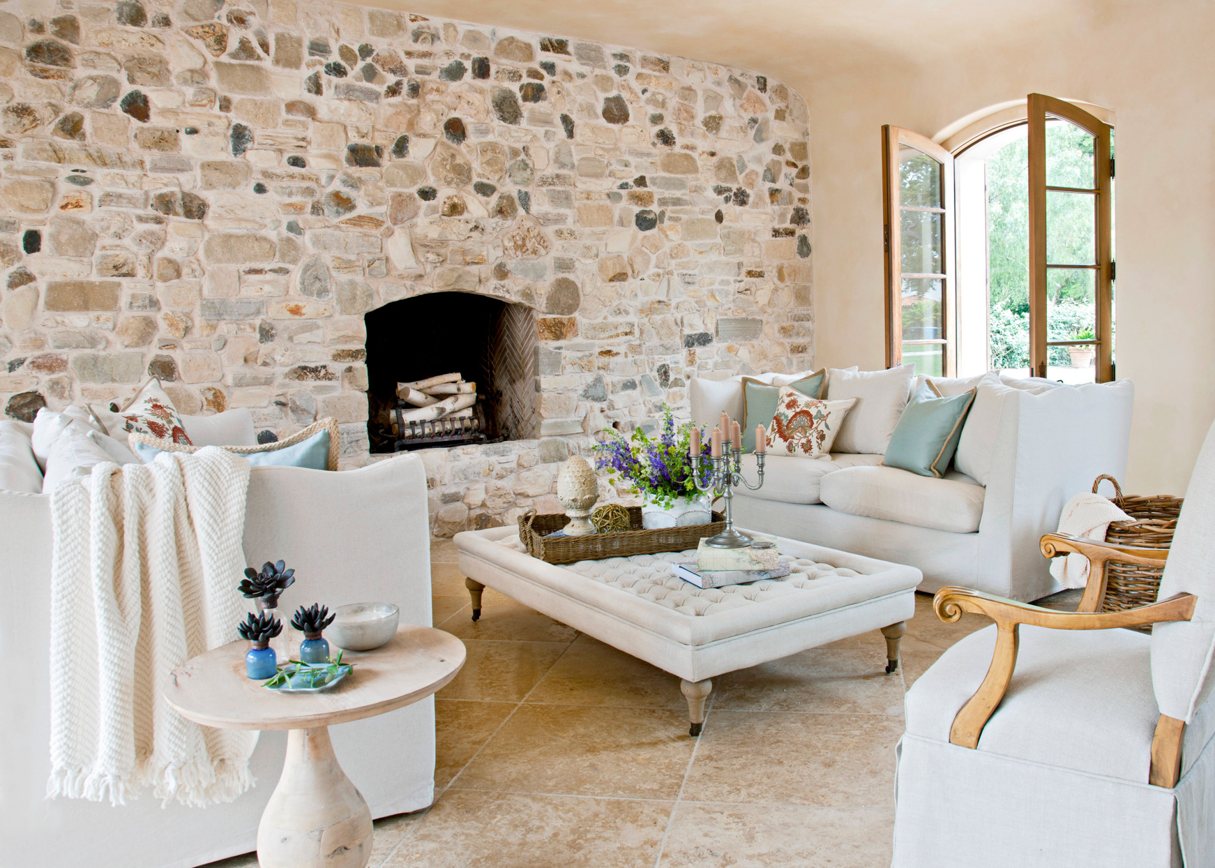 rustic stone fireplace with cream furniture