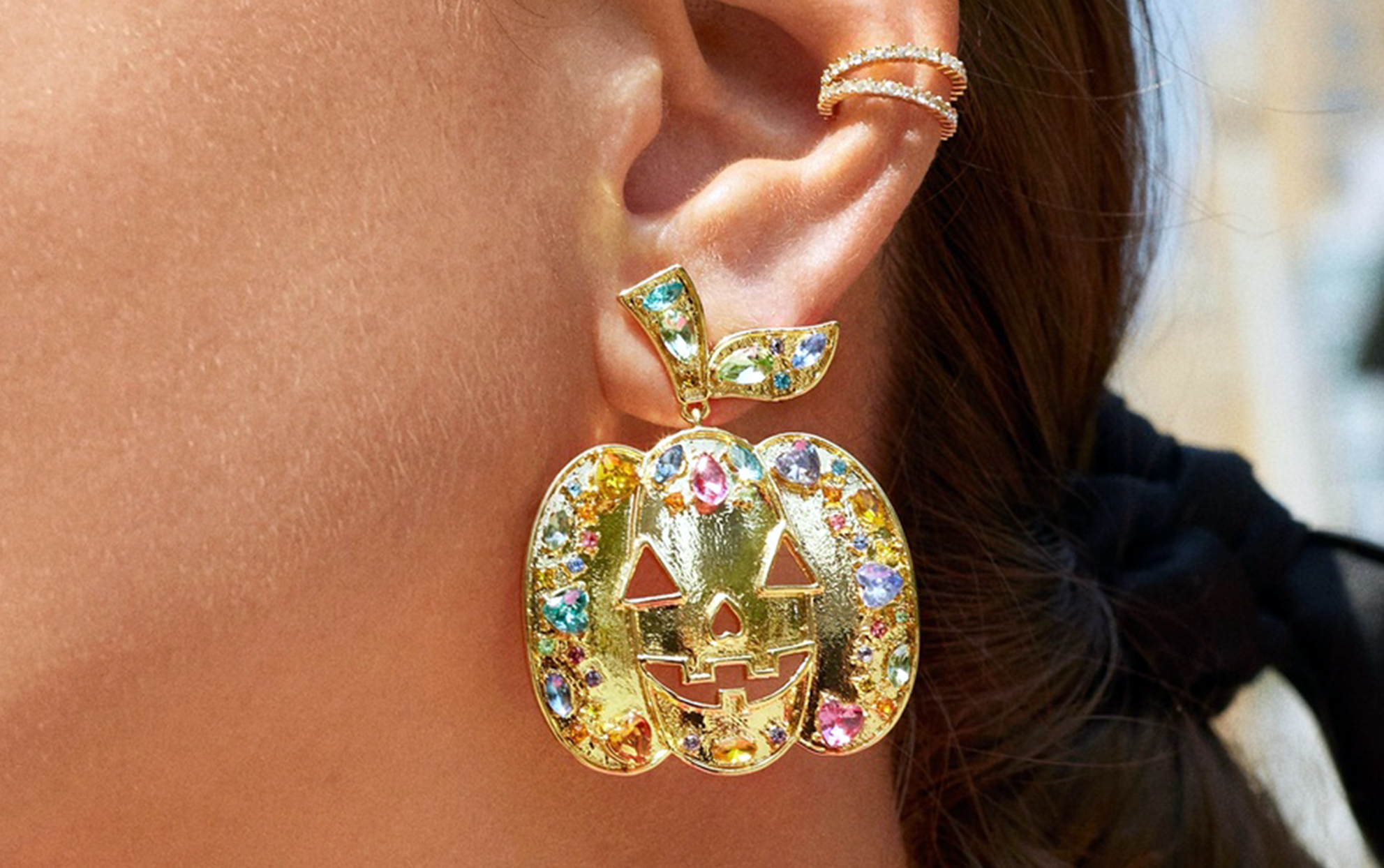 close up of pumpkin gold earrings on a woman