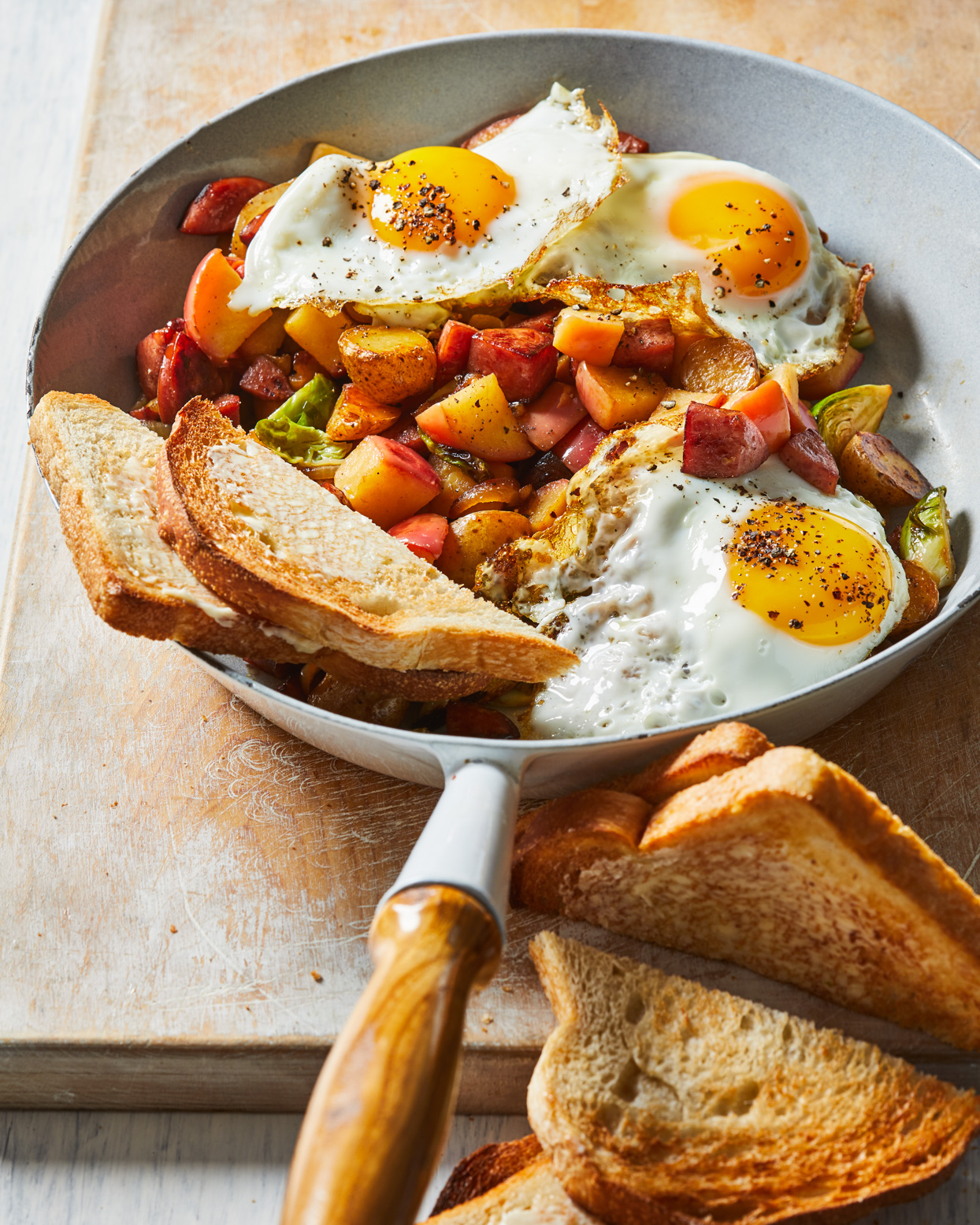 Apple-Kielbasa Hash in skillet topped with 3 fried eggs and toast