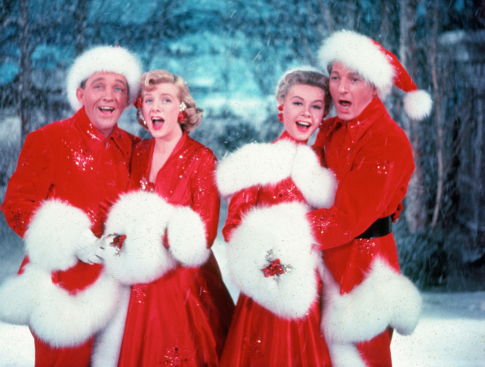 Bing Crosby, Rosemary Clooney, Vera-Ellen and Danny Kaye sing together, while dressed in fur-trimmed red outfits in a scene from the film White Christmas