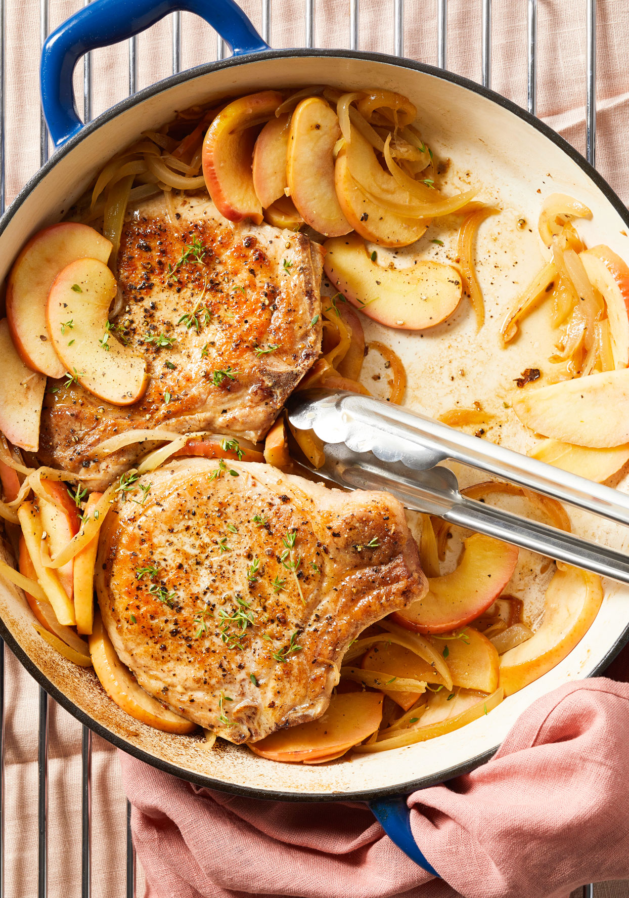 Tongs in blue skillet of Seared Pork Chops with Apples and Onion